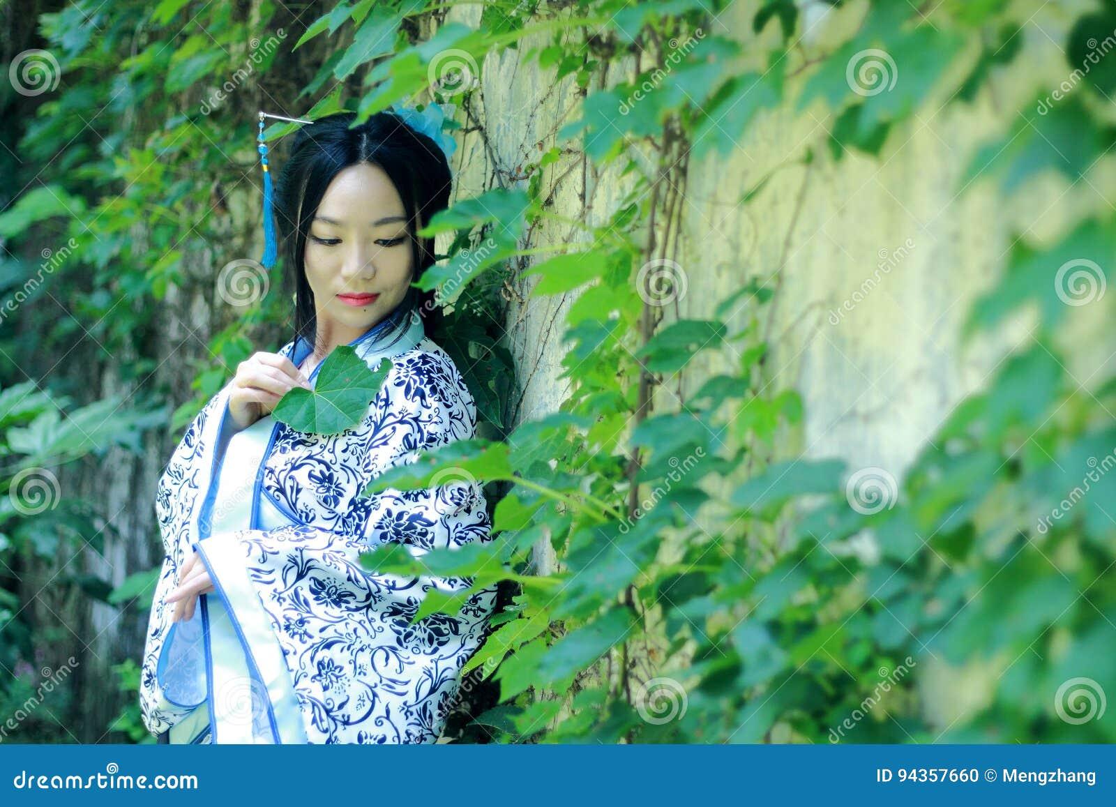 Donna cinese asiatica in vestito blu e bianco tradizionale da Hanfu, gioco in un giardino famoso vicino alla parete