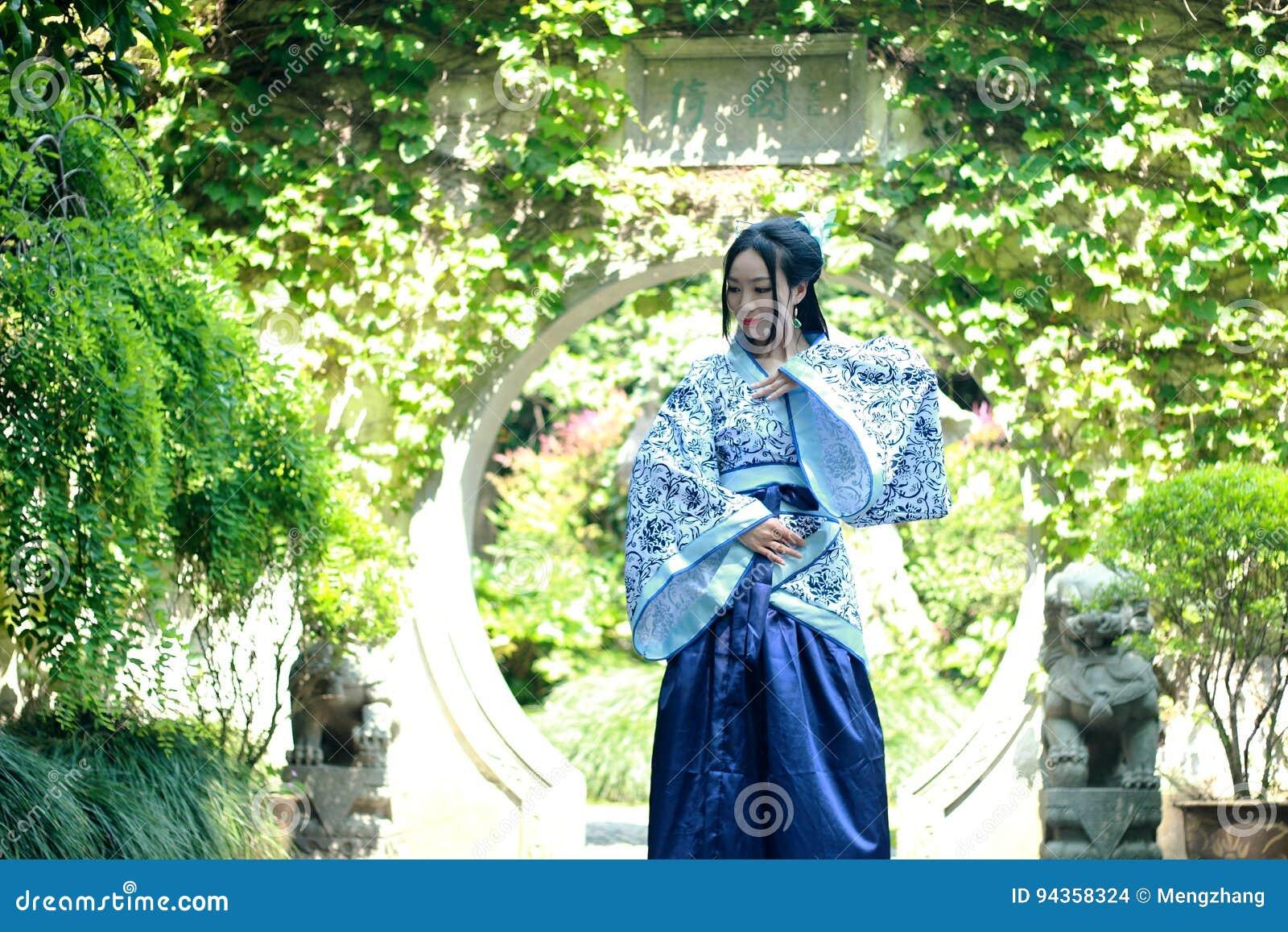Donna cinese in vestito blu e bianco tradizionale da Hanfu che sta in mezzo al bello portone