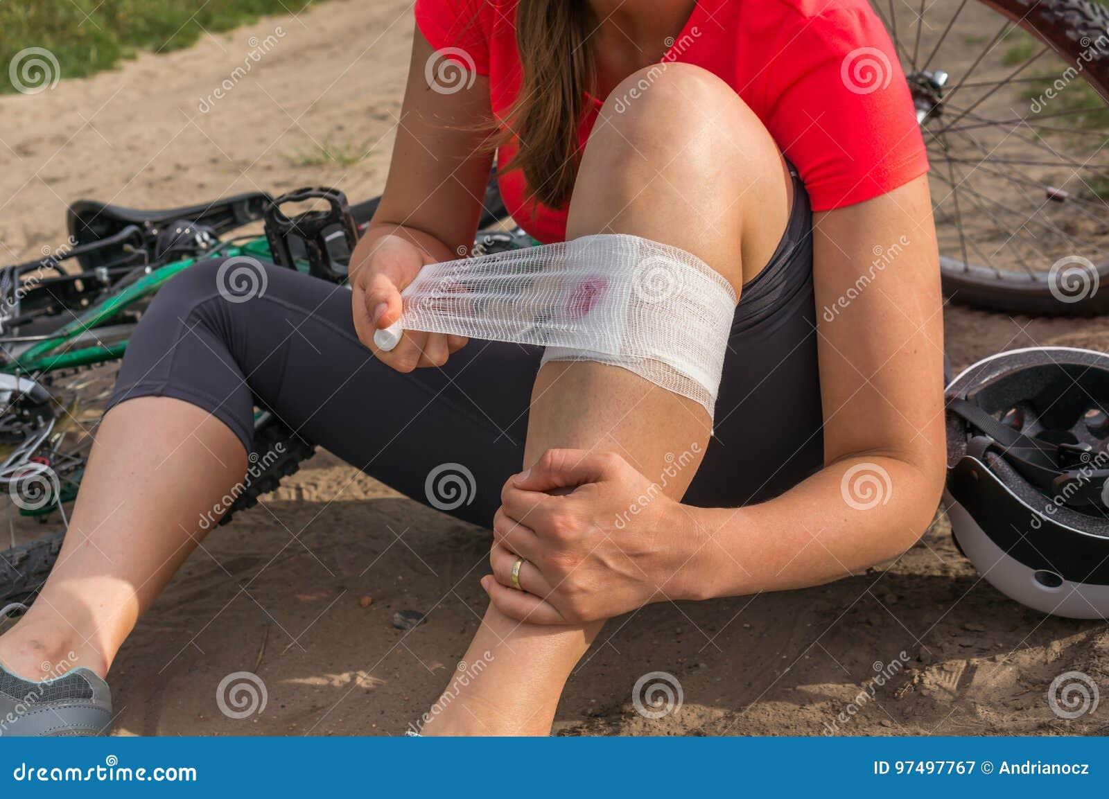 Donna con dolore in ginocchio dopo la caduta dalla bicicletta