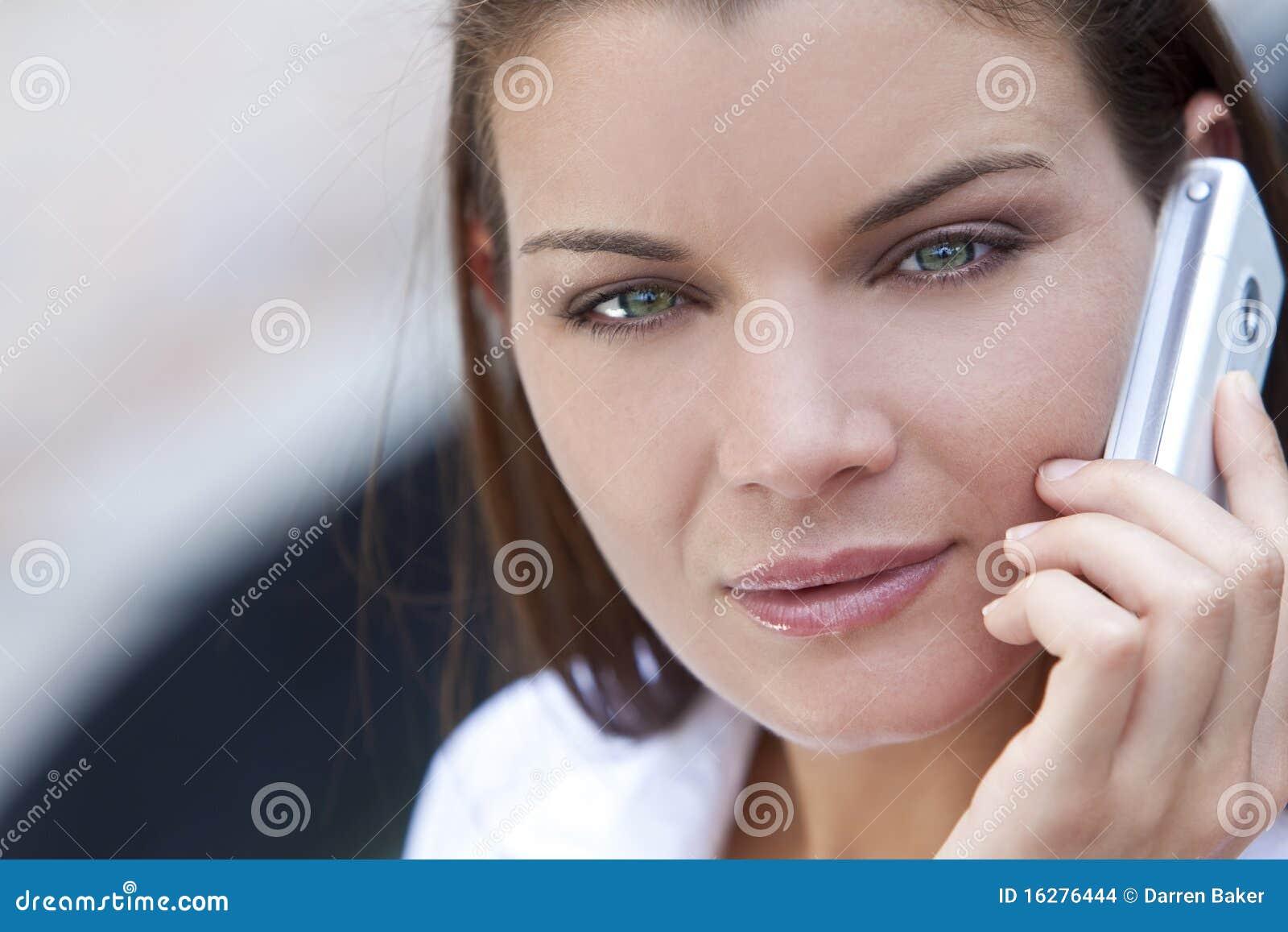 Gli occhi verdi che comunica sul suo telefono mobile delle cellule