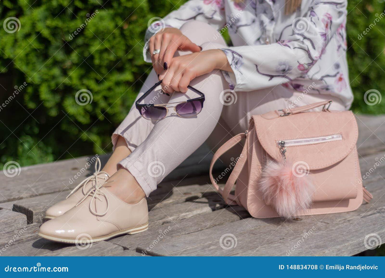 Donna con gli occhiali da sole in mani che si siedono su un banco accanto alla borsa rosa in un parco
