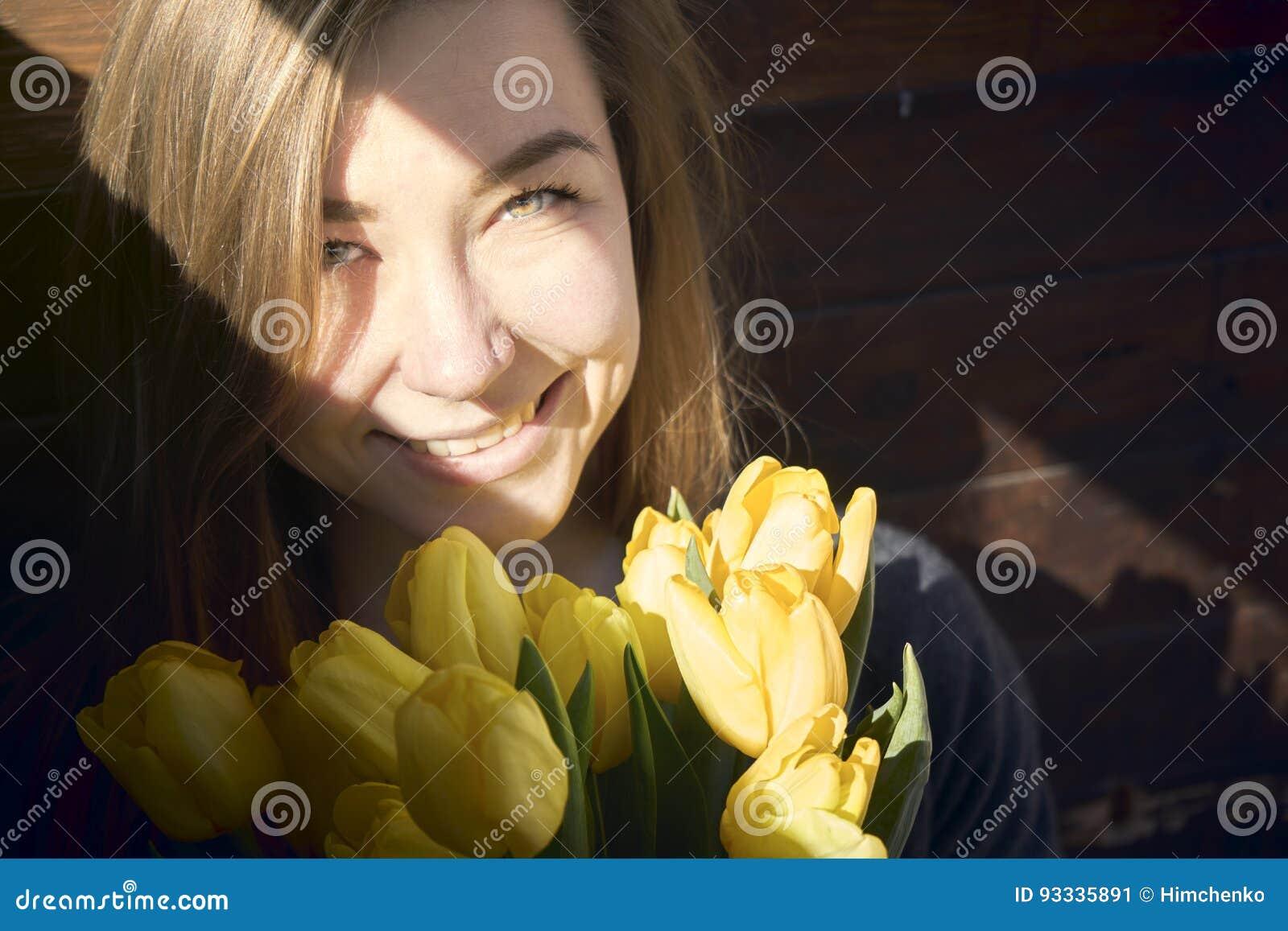 Donna con i fiori in una stanza scura