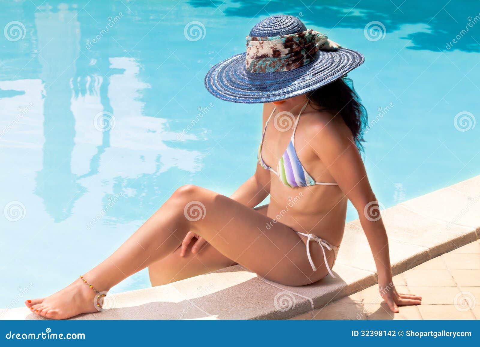 Donna Con Il Cappello Blu Che Si Abbronza Nella Piscina Fotografia Stock - Im...
