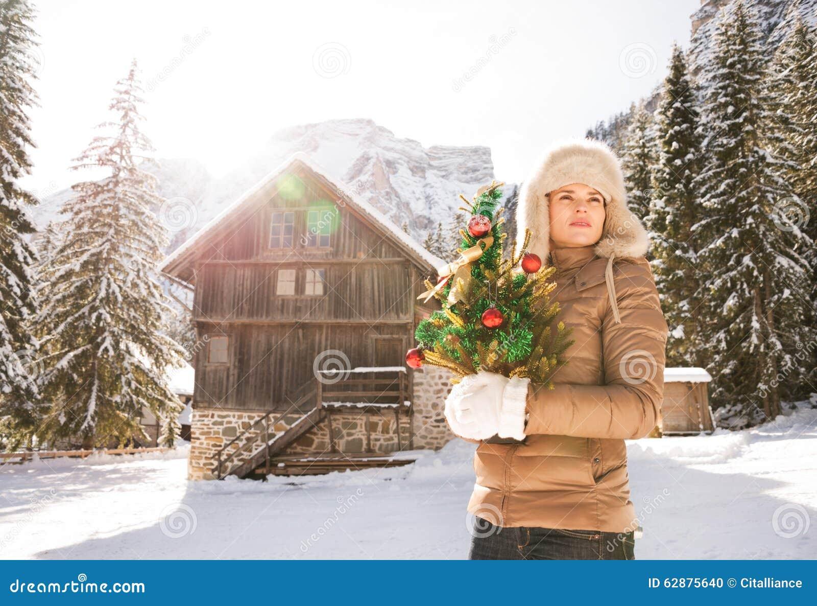 Donna con l 39 albero di natale che sta davanti alla casa for Planimetrie della casa di montagna