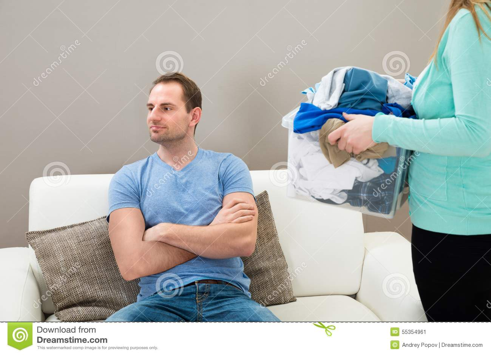 Donna con la lavanderia mentre uomo sul sofà