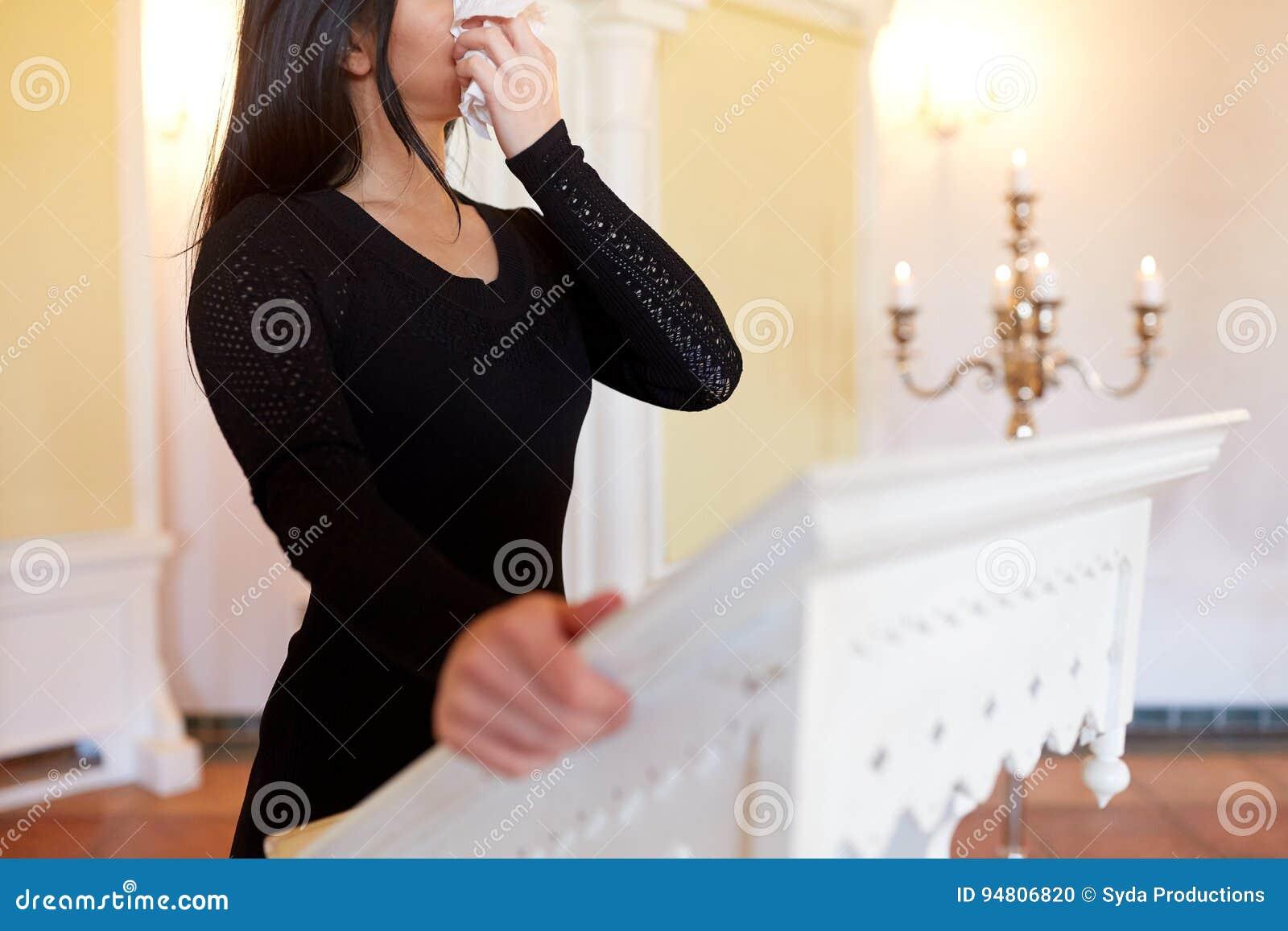 Donna con la strofinata che grida al funerale in chiesa