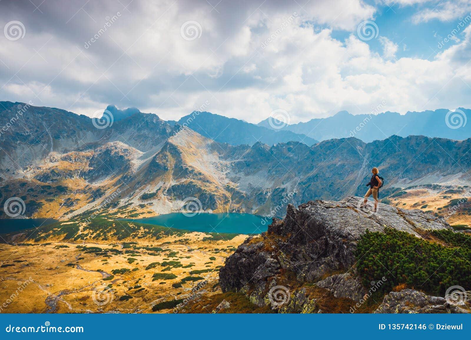 Donna con lo zaino che sta sopra una montagna