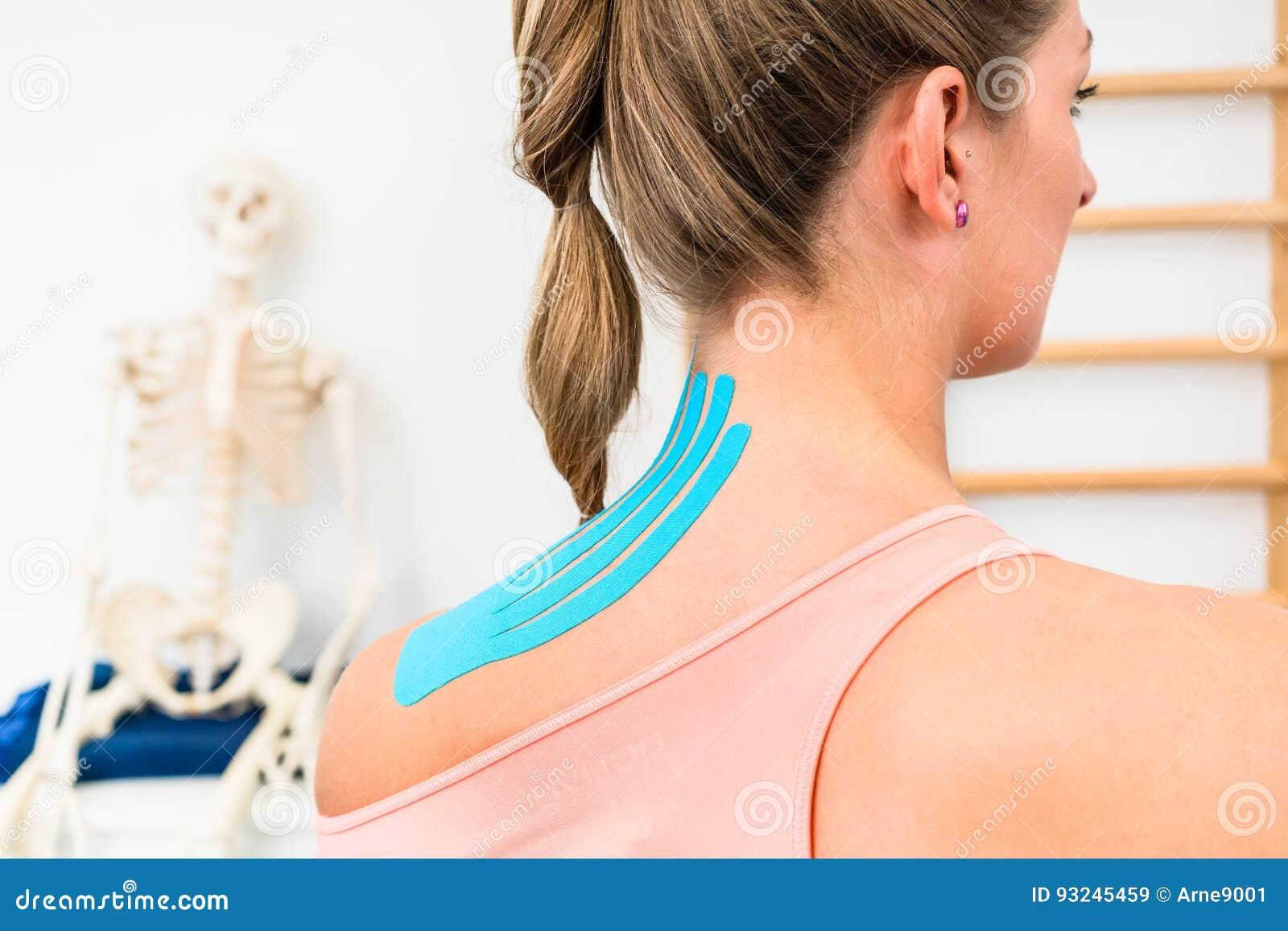 Donna con nastro adesivo di Kinesio sulla spalla in fisioterapia