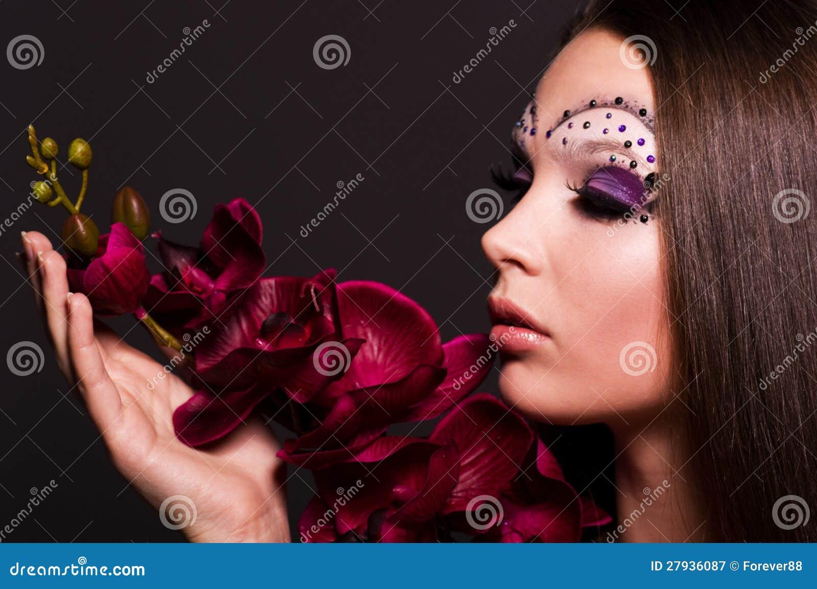 Donna con trucco e l orchidea