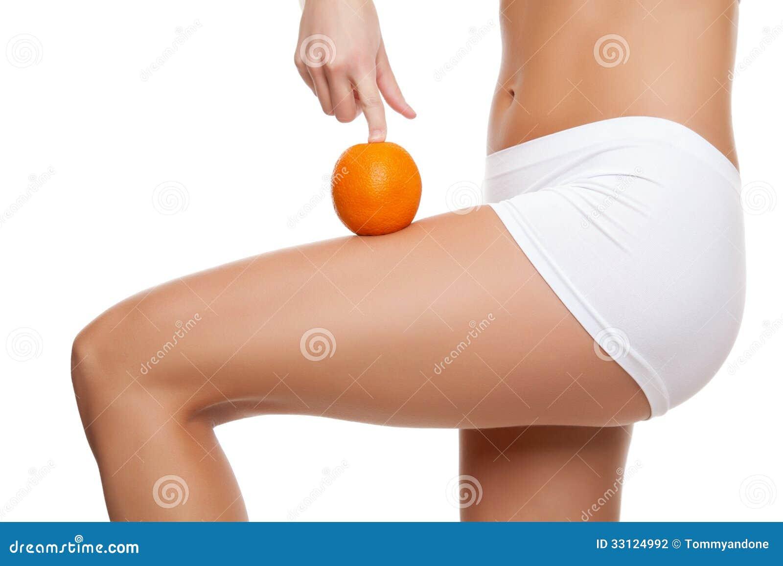 Donna con un arancia che mostra una pelle perfetta