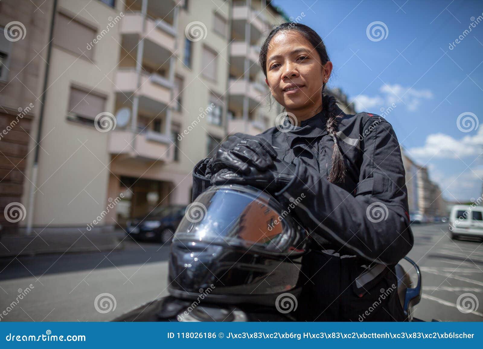 Donna con un casco nero su una motocicletta
