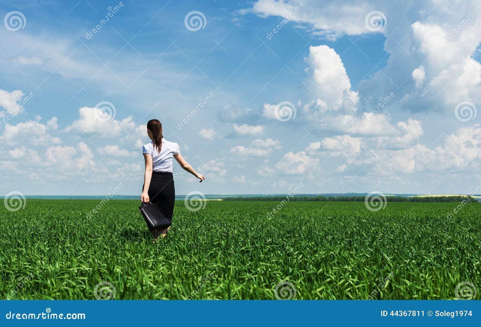 Donna con una cartella che cammina sull erba