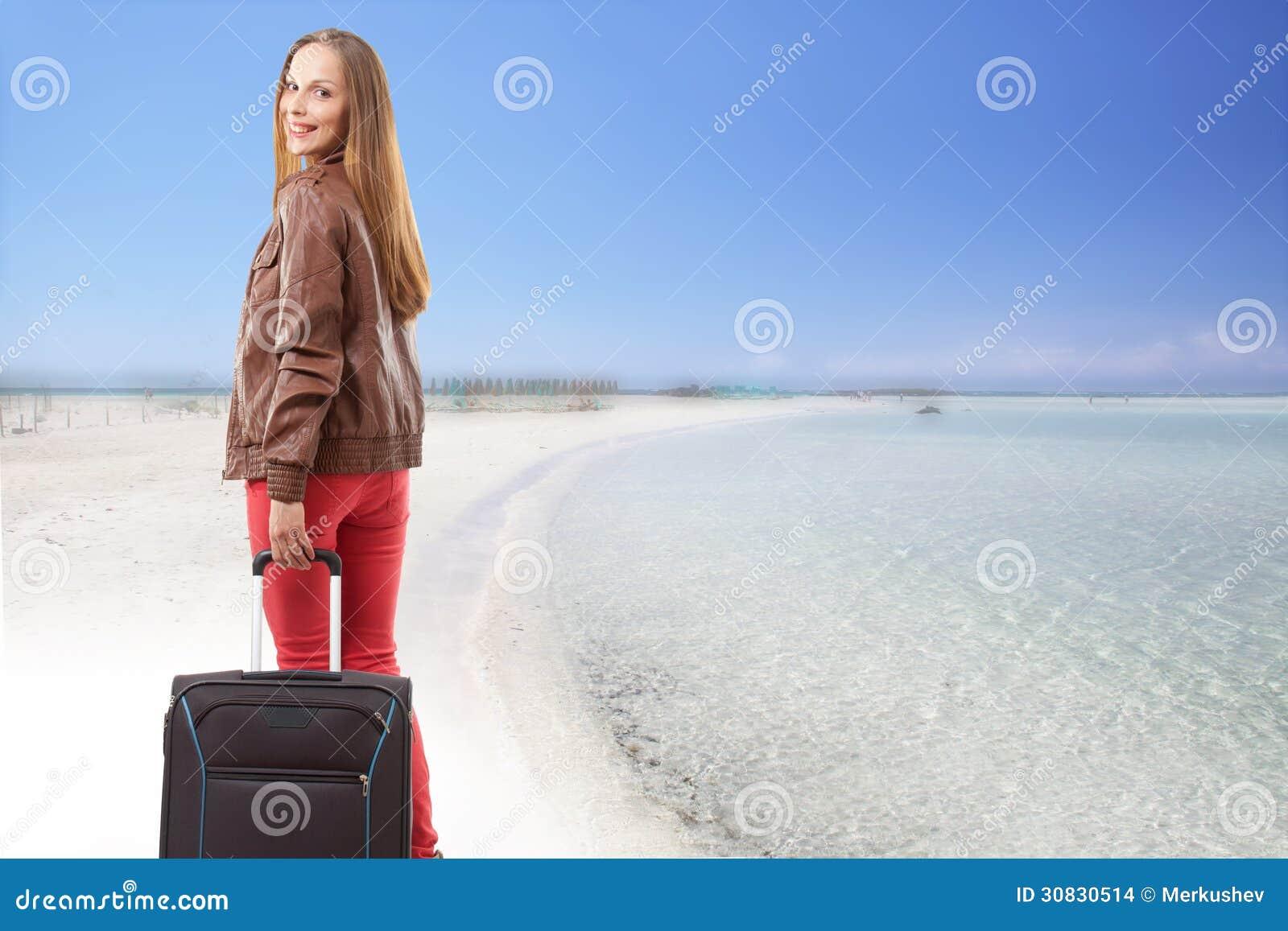 Donna con una valigia sulla spiaggia