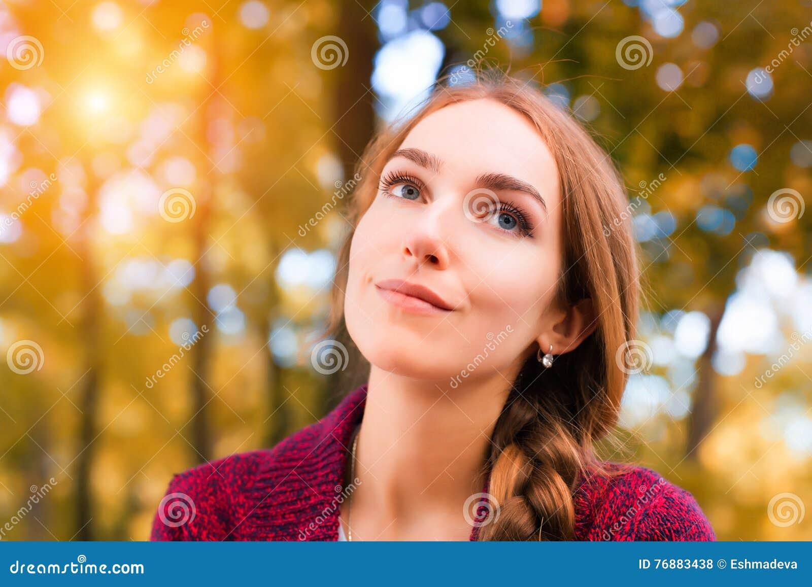 Donna contro il fondo soleggiato di autunno