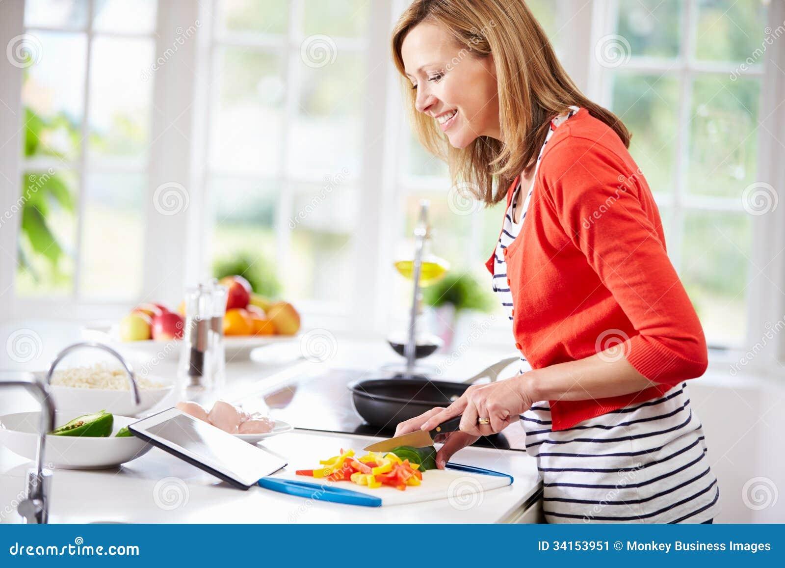 Donna in cucina a seguito della ricetta sulla compressa di Digital