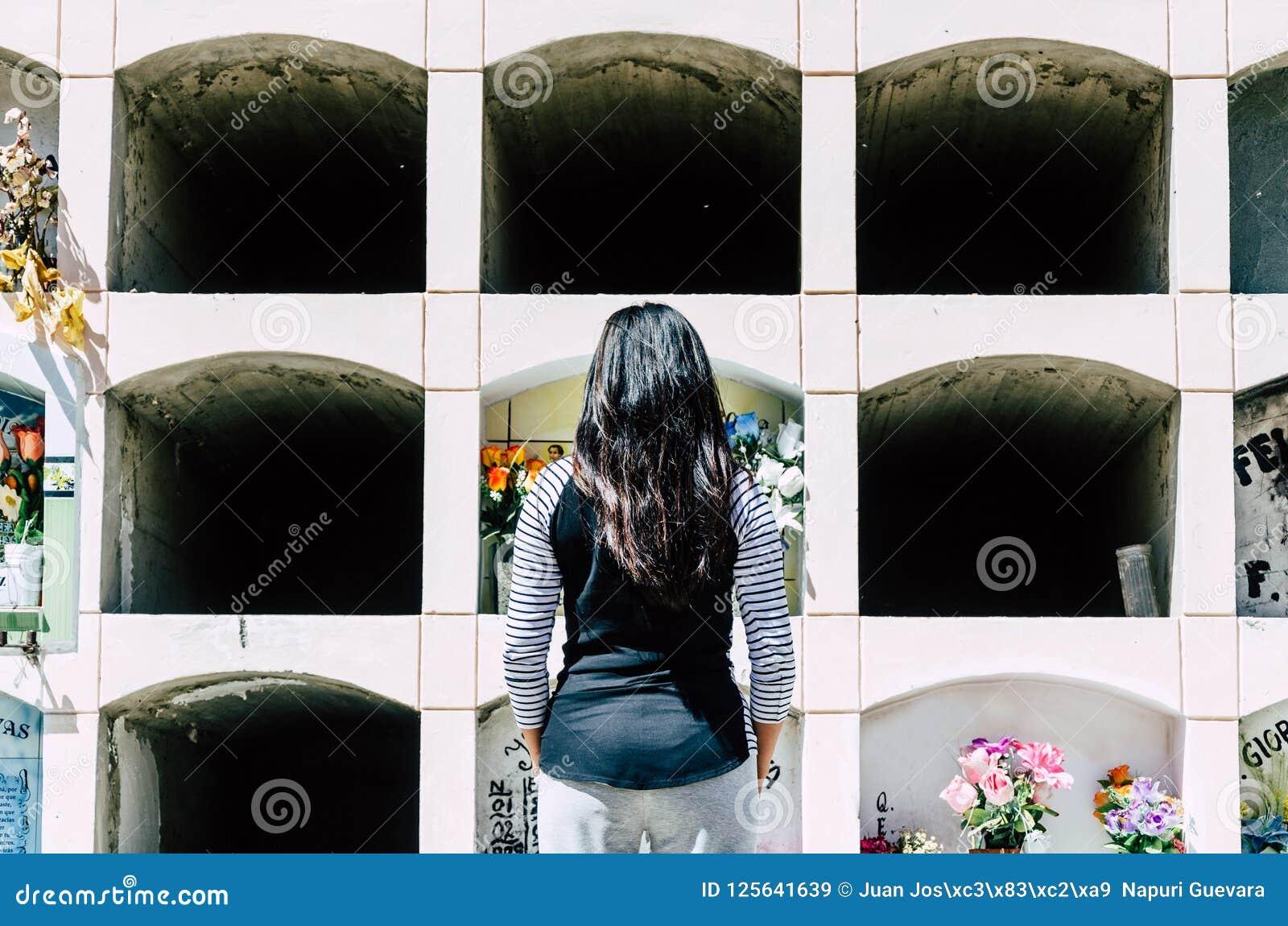 Donna da dietro contemplando la tomba di un caro