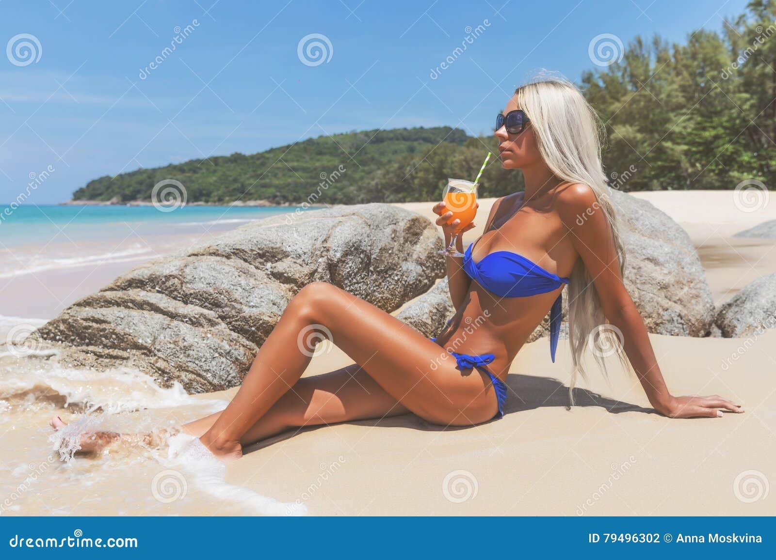 Donna dai capelli lunghi bionda esile in bikini sulla spiaggia tropicale