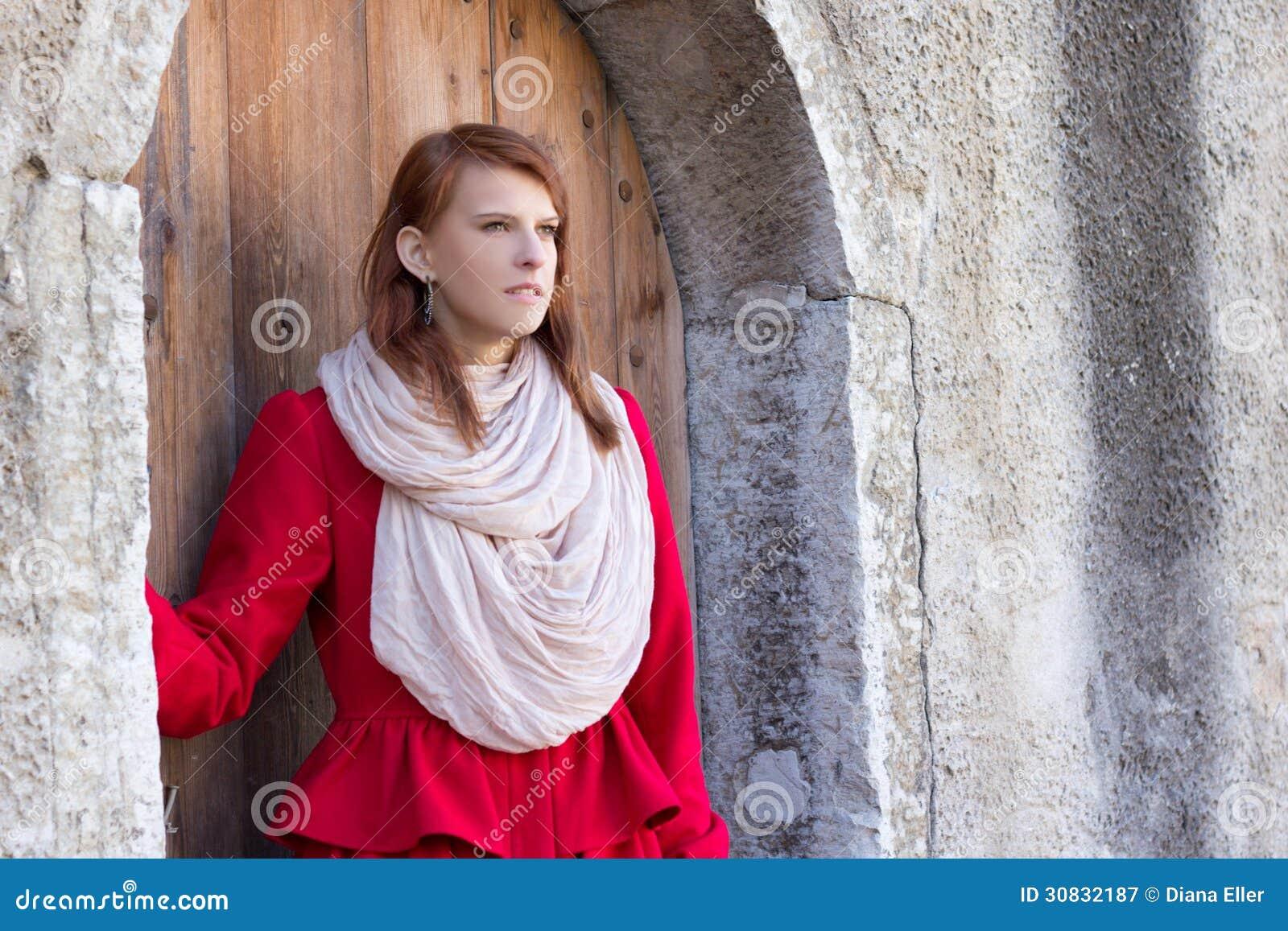 Donna dai capelli rossi che posa davanti alla vecchia porta