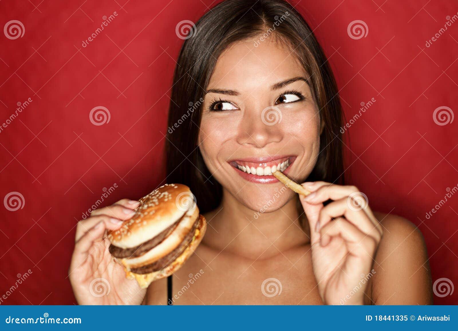 Donna degli alimenti industriali che mangia hamburger