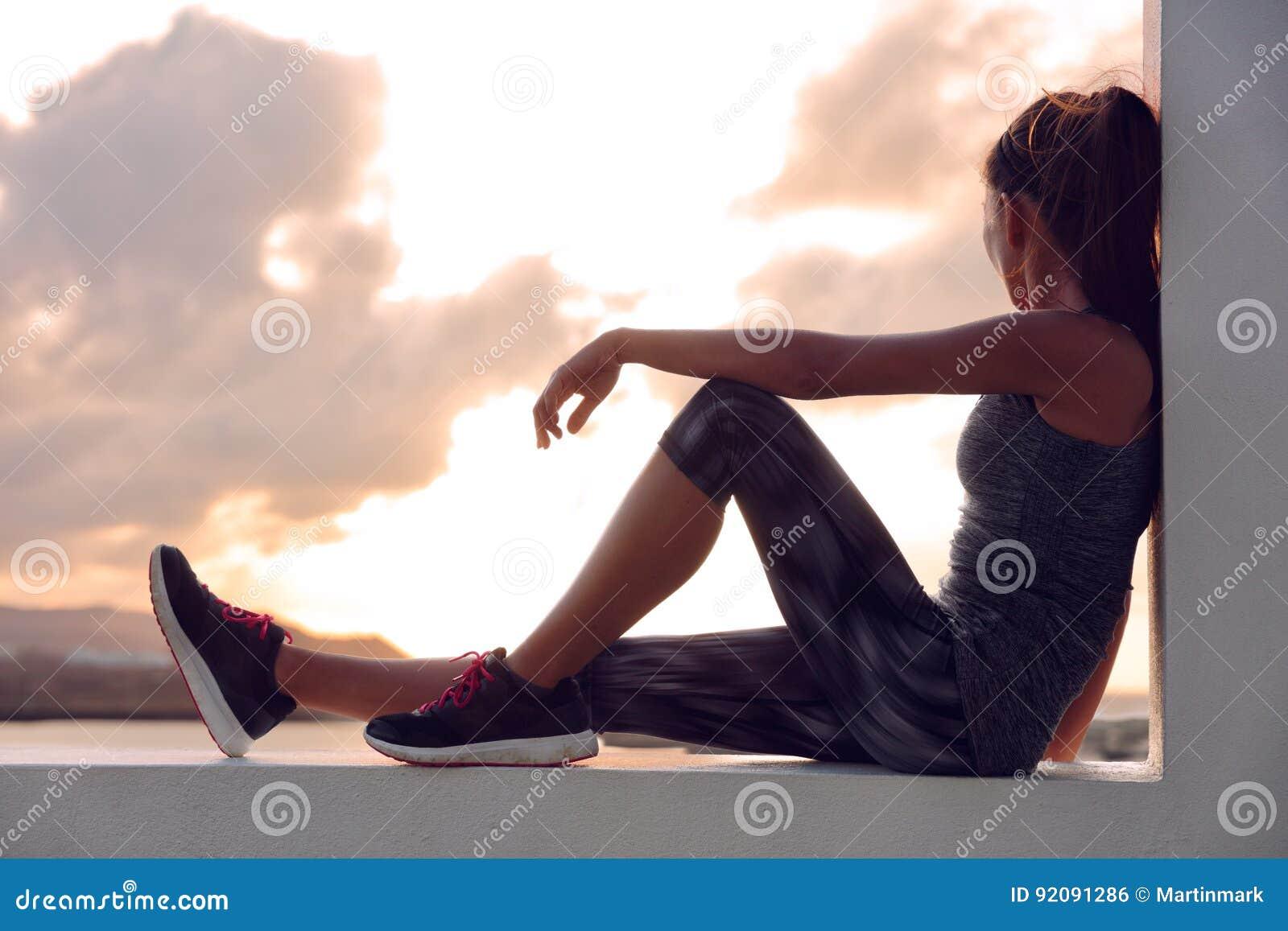 Donna del corridore dell atleta di forma fisica che si rilassa nel tramonto