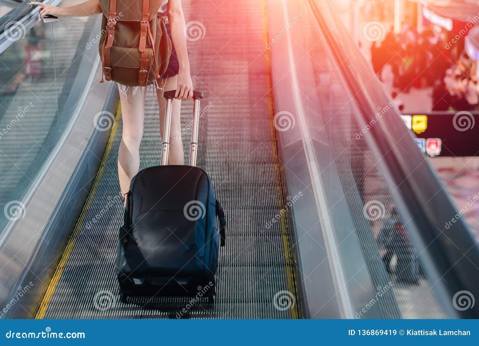 Donna del Midsection con bagagli che viaggiano all aeroporto