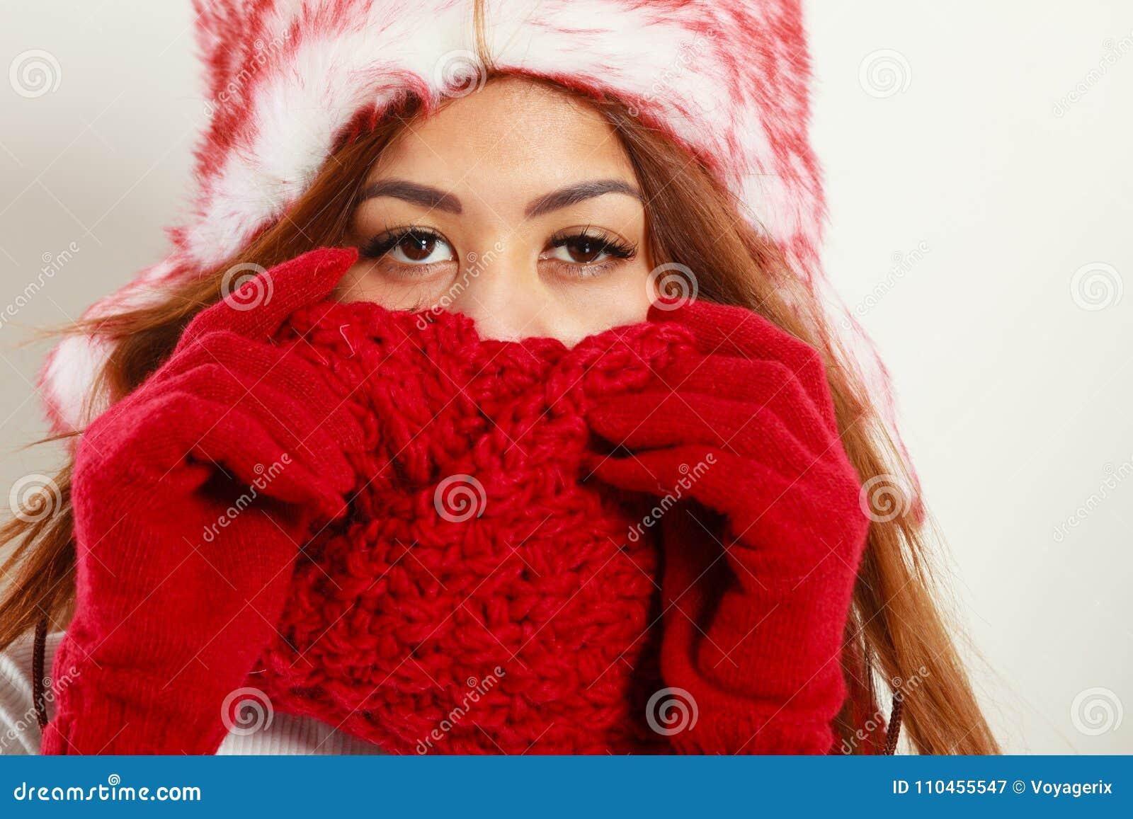 a87d42d6cf1c Abbigliamento di inverno, concetto di modo Primo piano di giovane donna del  mulatto che copre il suo fronte di mani che portano i guanti e sciarpa  rossi La ...