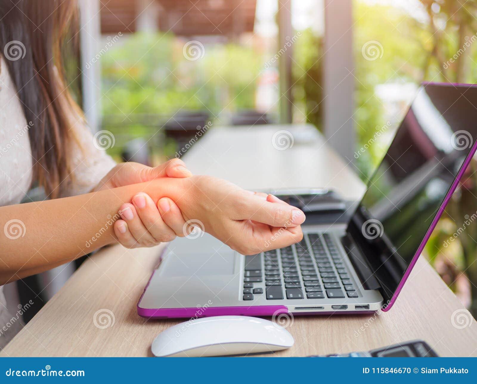 Donna del primo piano che tiene il suo dolore del polso dal per mezzo del computer
