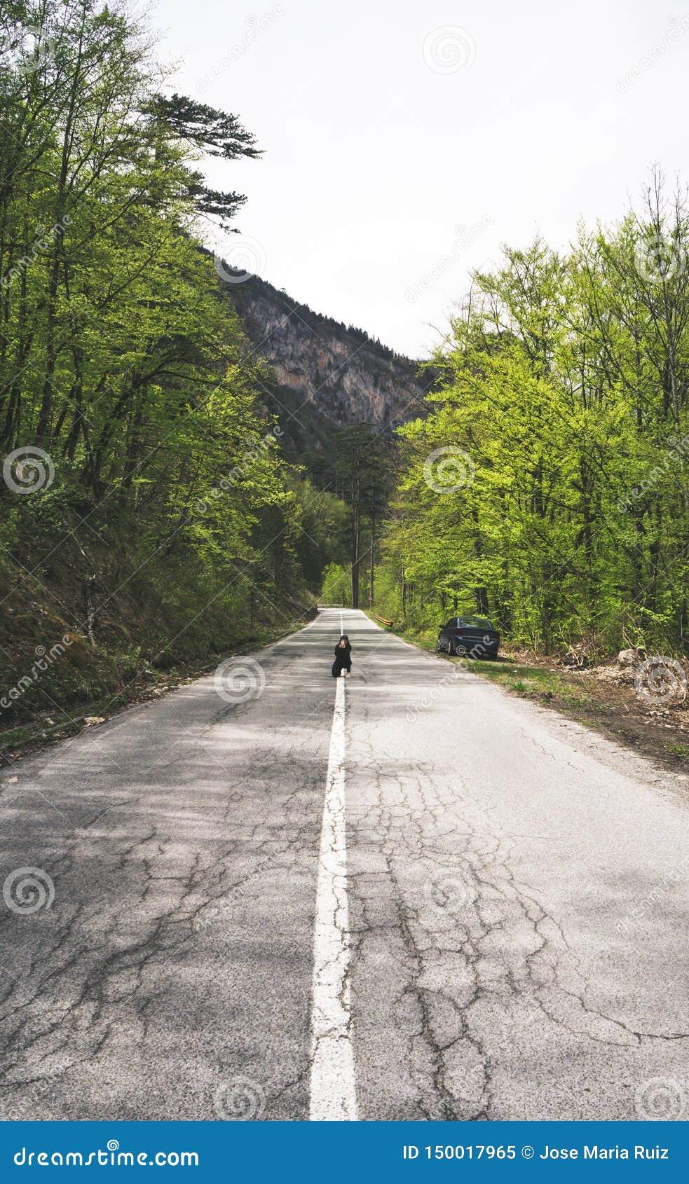 Donna del viaggiatore che per mezzo dello smartphone che prende la campagna della strada delle immagini e naturale europei il gio