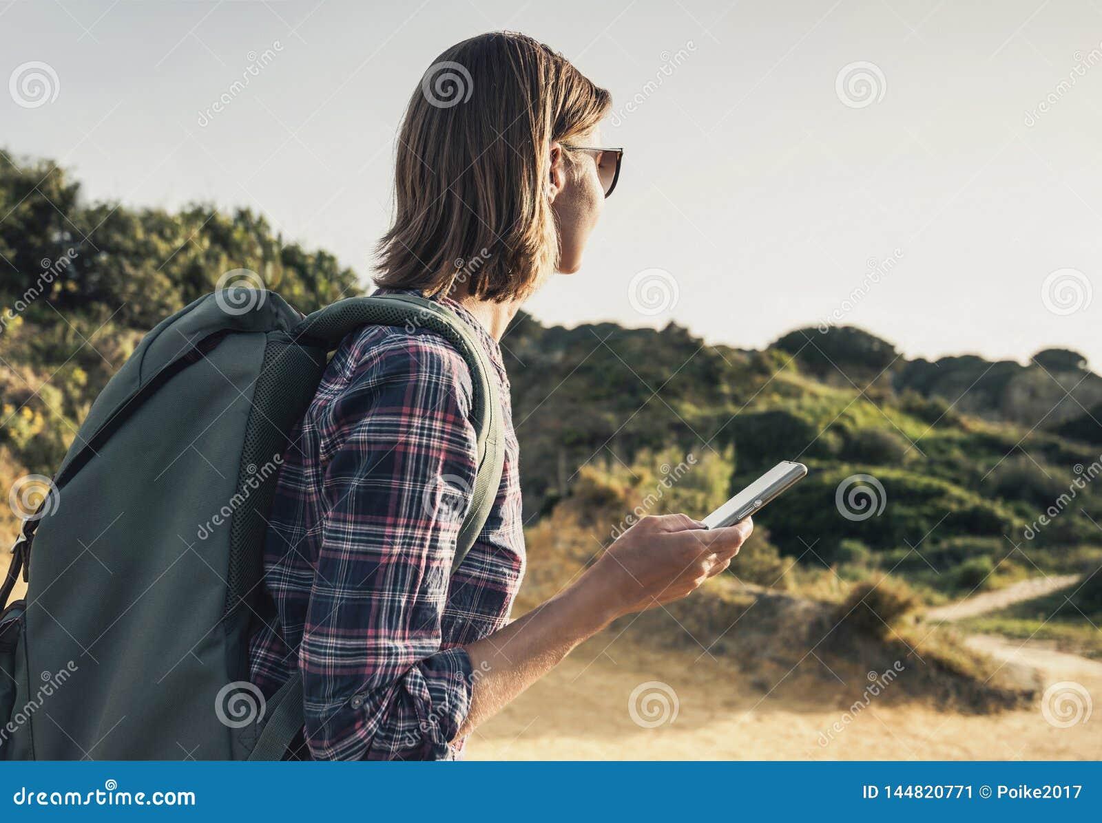 Donna del viaggiatore della viandante su una traccia di escursione facendo uso dello smartphone, del viaggio e del concetto attiv