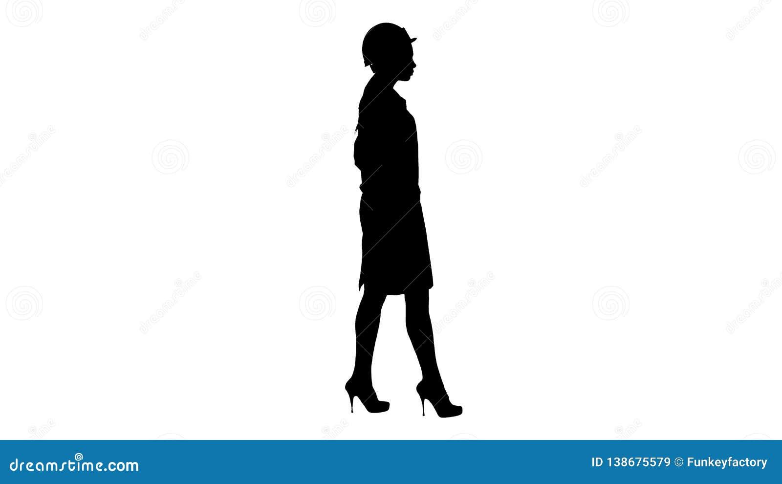 Donna della siluetta in abito bianco che mette casco su mentre camminando
