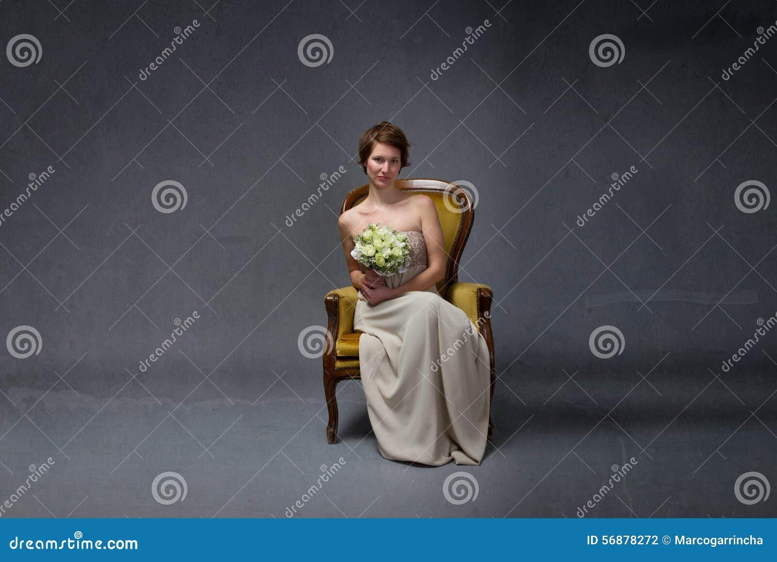 Donna della sposa che si siede sul sofà giallo