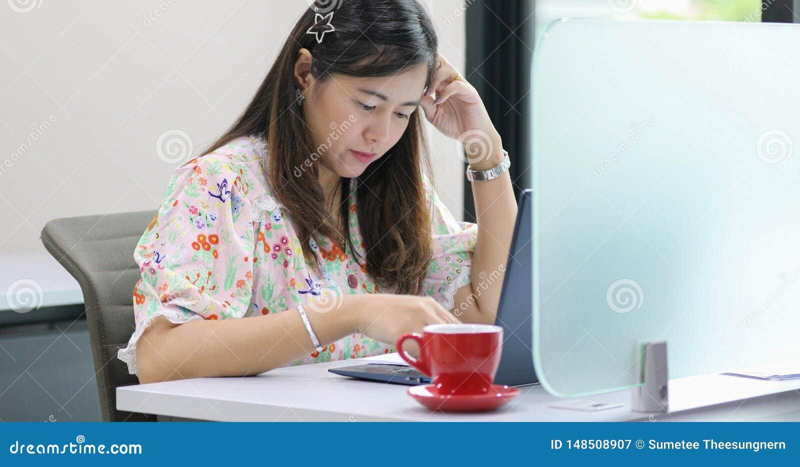 Donna di affari asiatica seria circa il lavoro e che per mezzo del taccuino per i soci commerciali che discutono i documenti e le