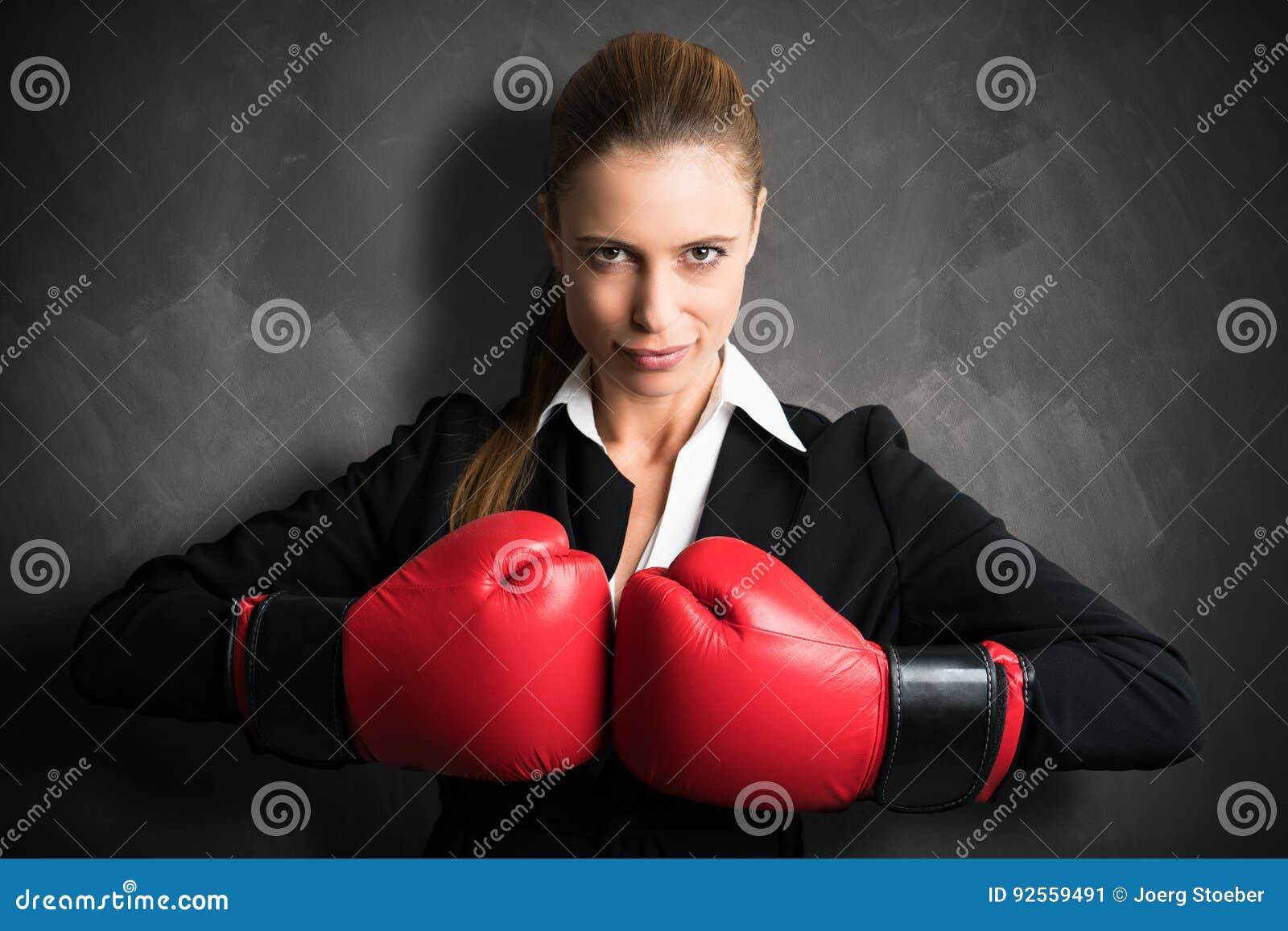 Donna di affari attraente con i guantoni da pugile pronti per una lotta