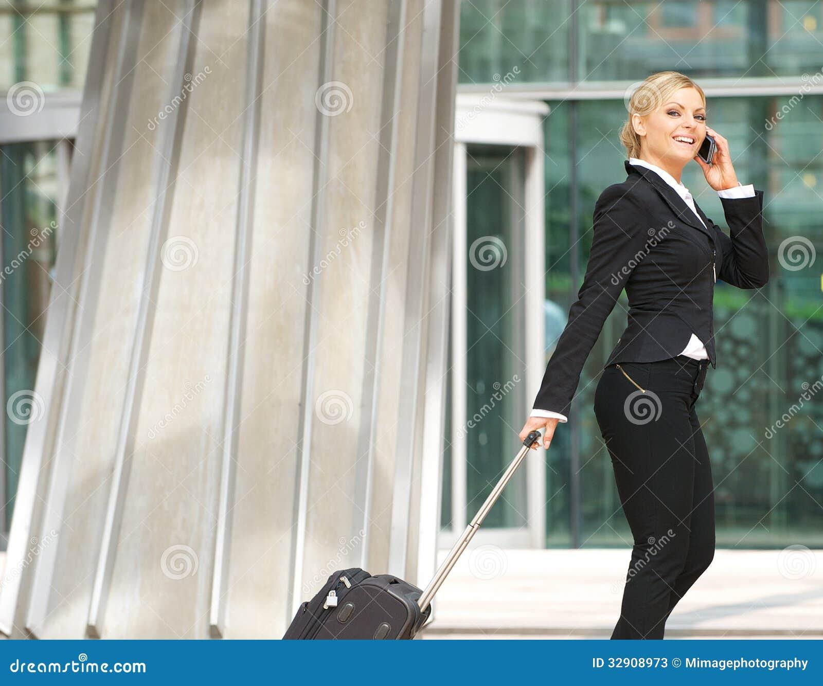 Affari che cammina con la valigia e che parla sul telefono cellulare