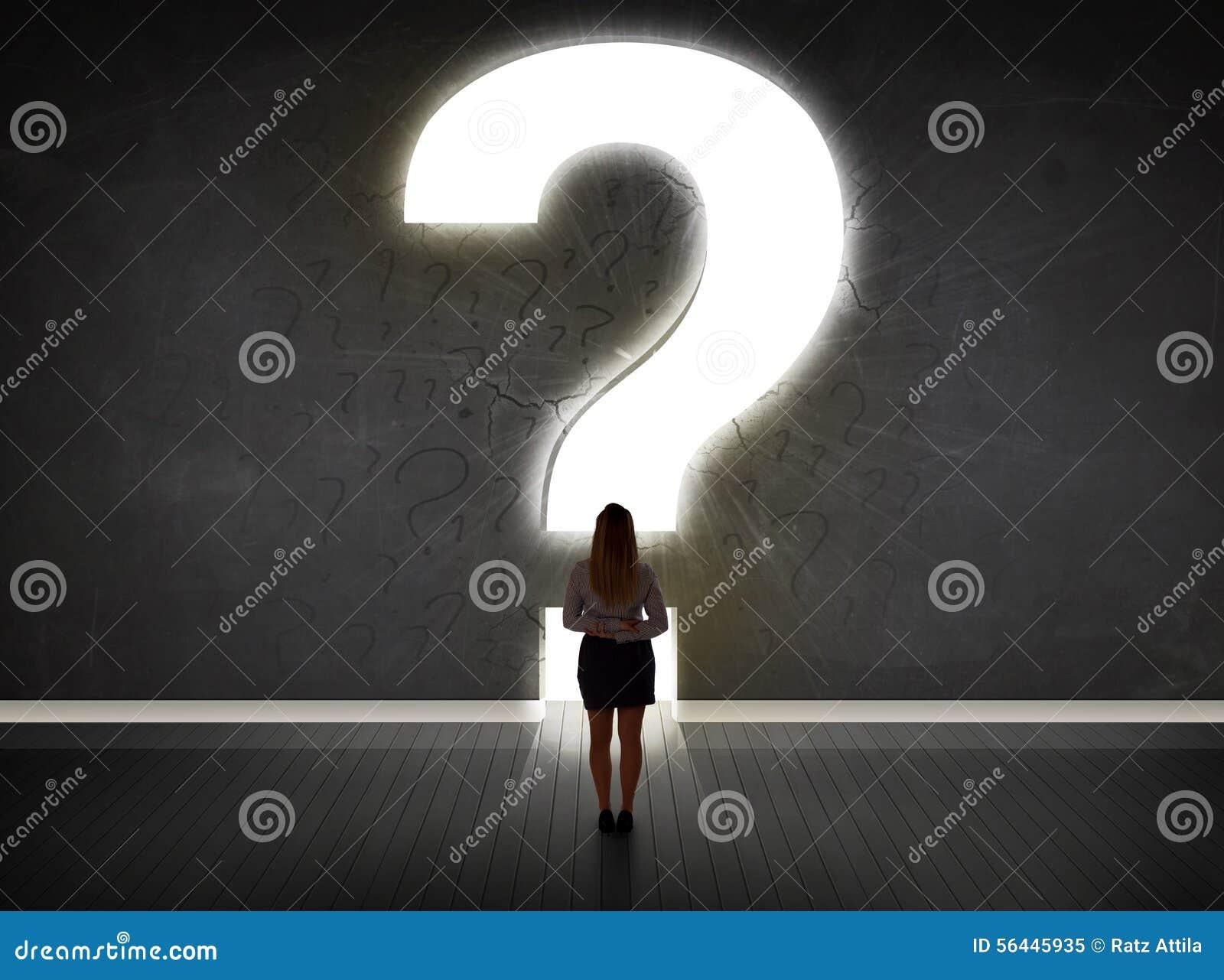 Donna di affari che esamina parete con un punto interrogativo luminoso