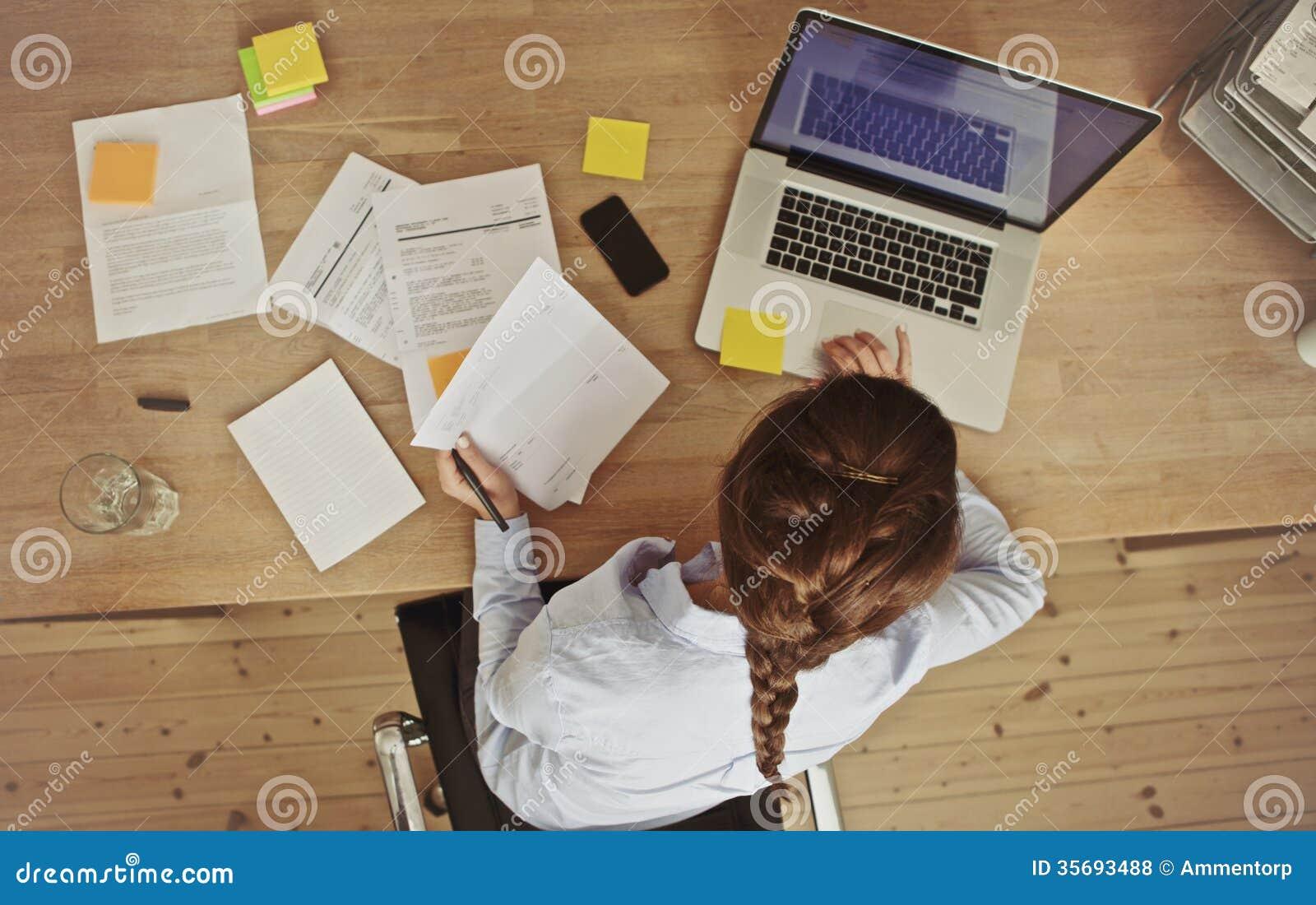 Donna di affari che lavora alla sua scrivania con i documenti ed il computer portatile