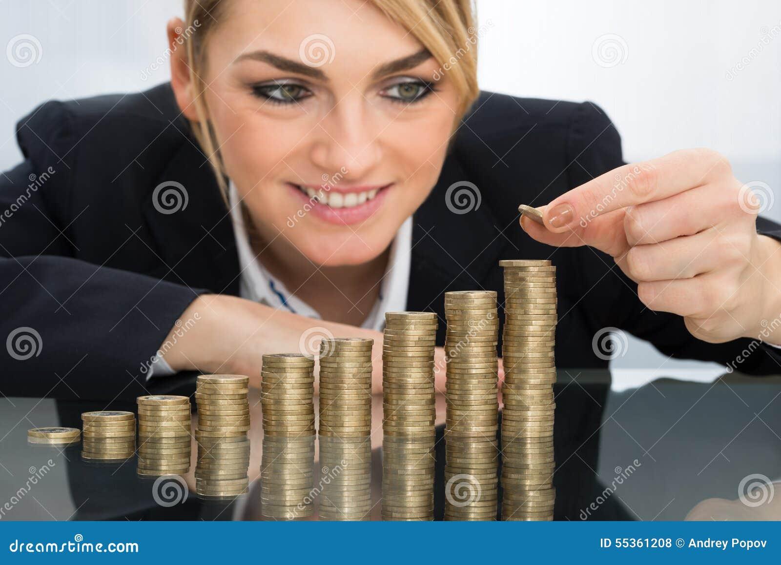 Donna di affari che mette moneta sulla pila di monete