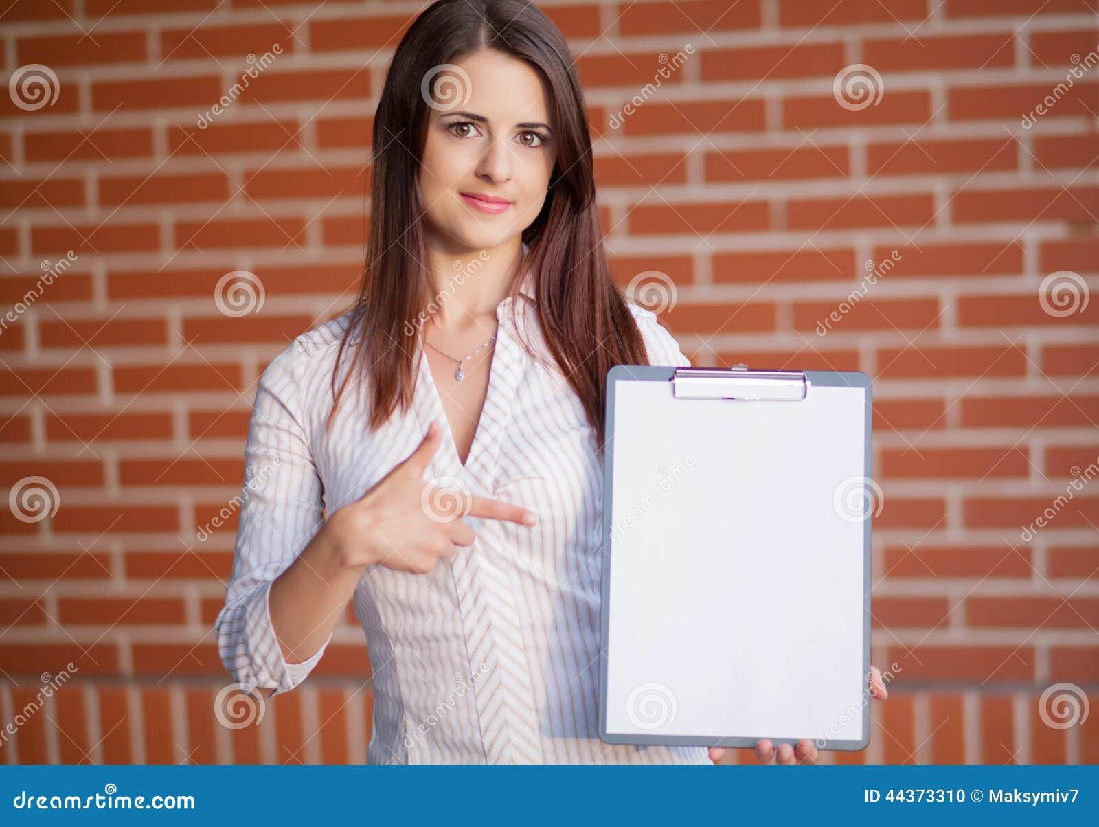 Donna di affari che mostra lavagna per appunti in bianco