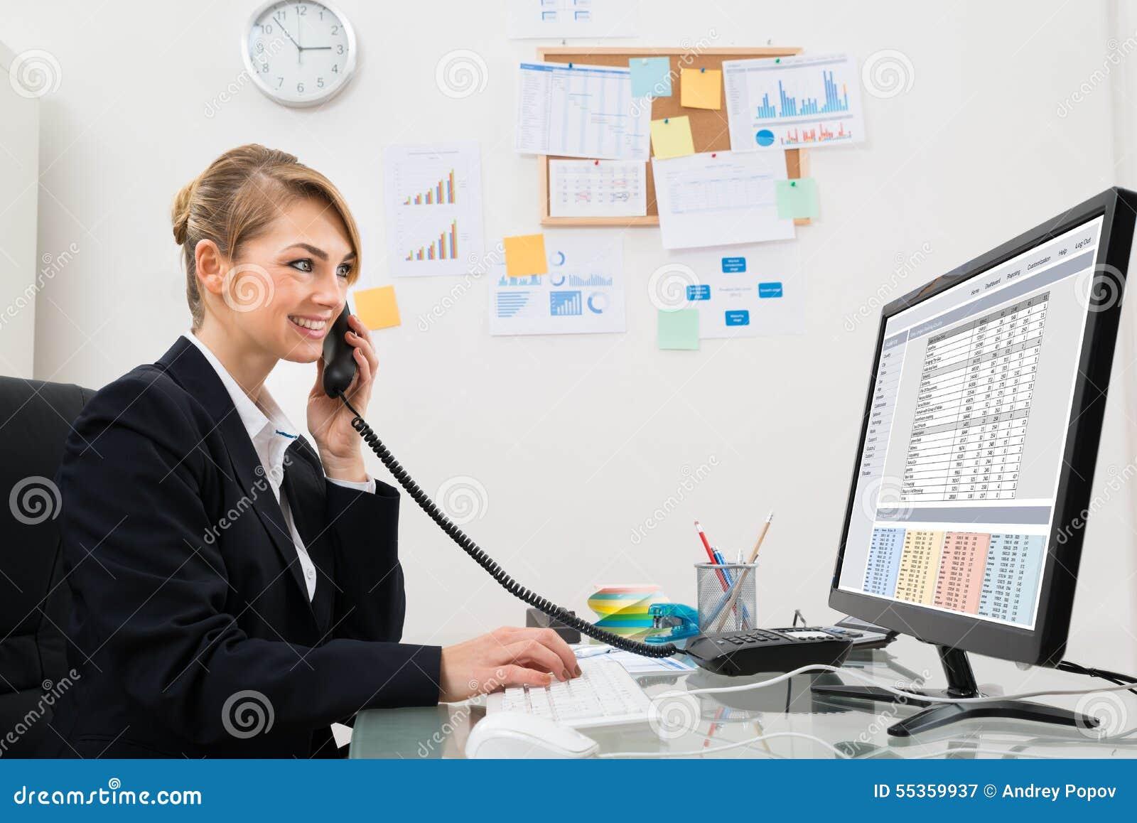 Donna di affari che parla sul telefono allo scrittorio