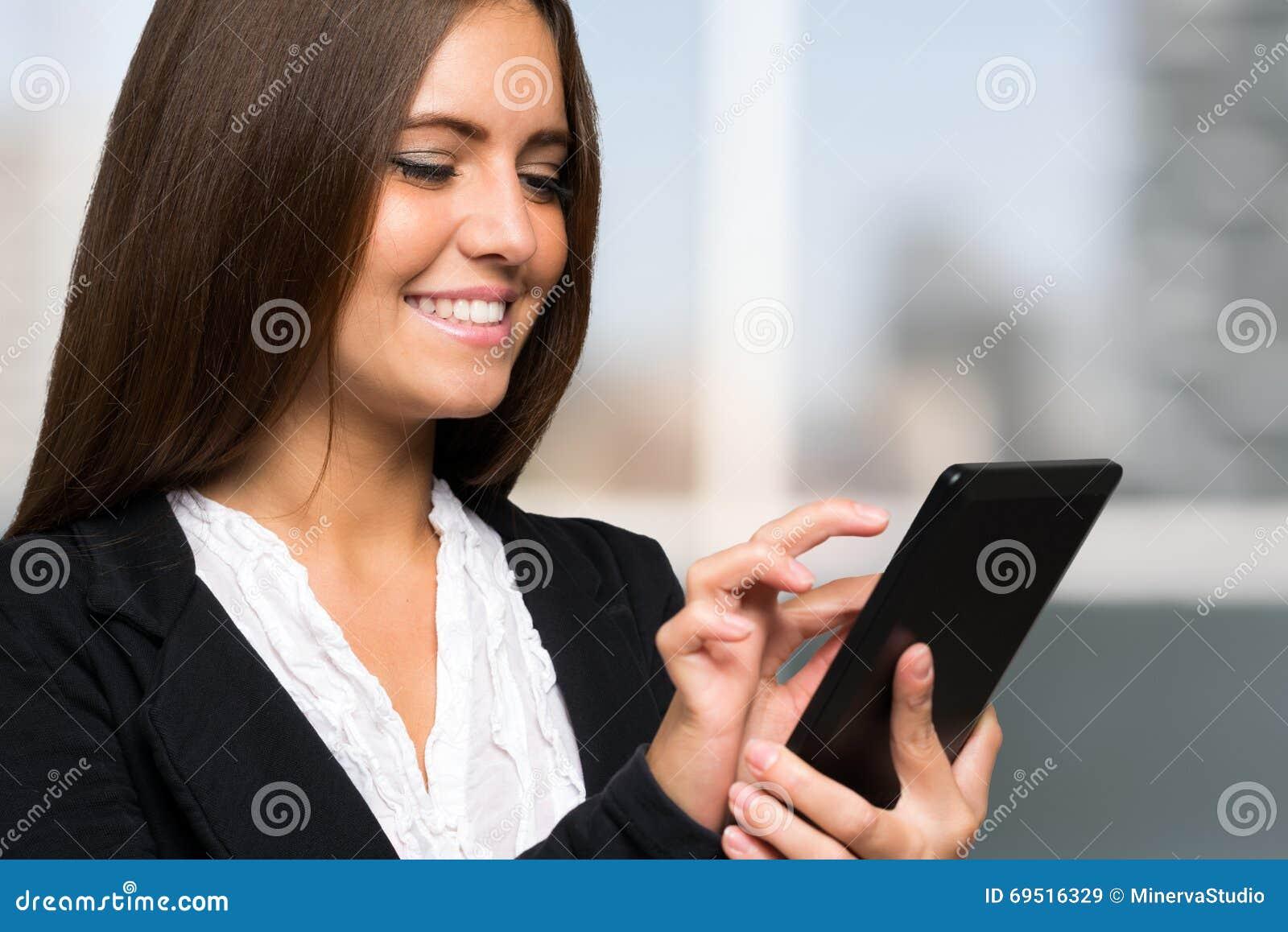 Donna di affari che per mezzo di una compressa digitale