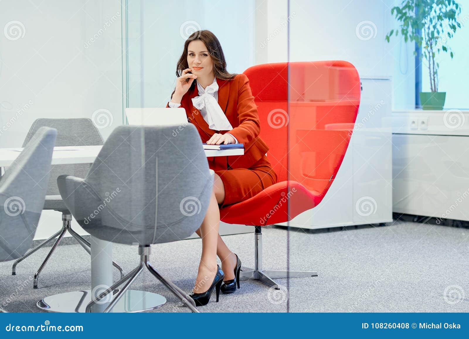 Donna di affari che si siede su una sedia rossa in un ufficio di vetro e negli impianti