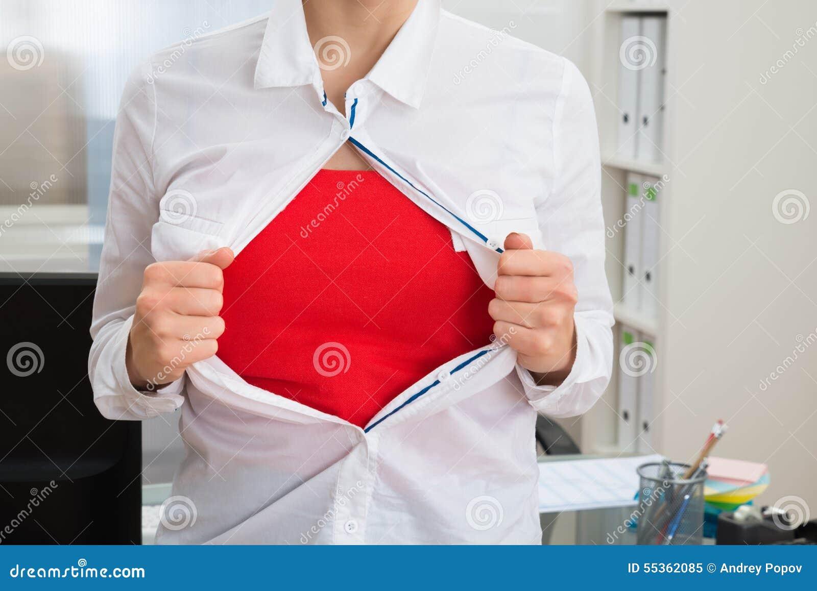 Donna di affari che strappa la sua camicia che mostra costume rosso
