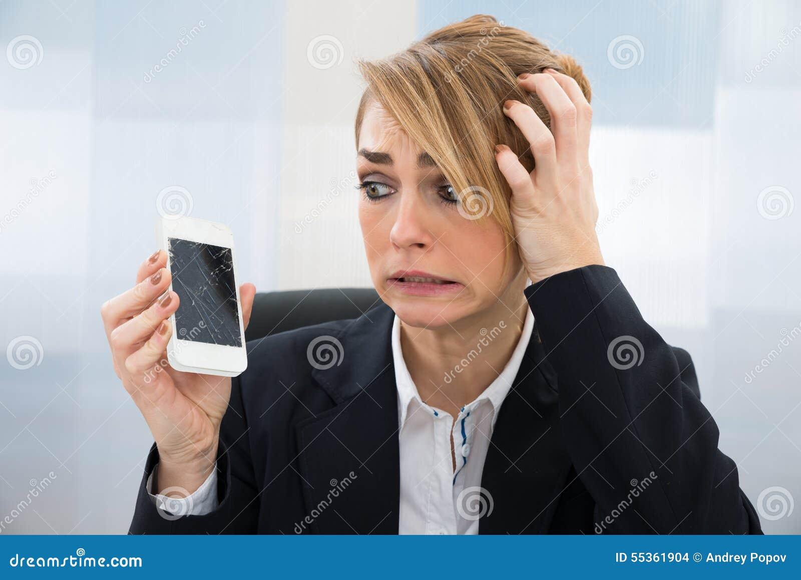 Donna di affari che tiene smartphone tagliato