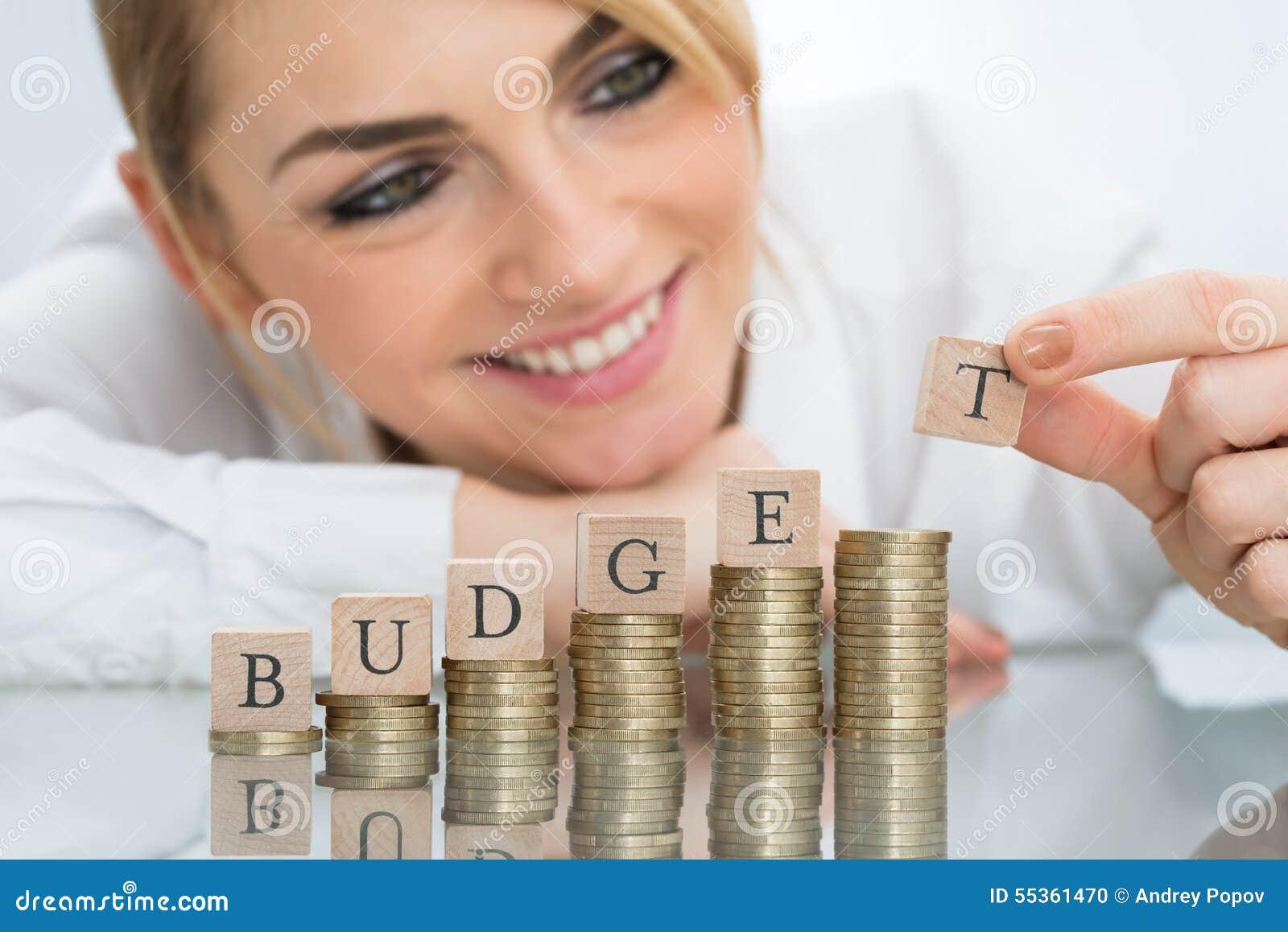 Donna di affari con i blocchetti del bilancio sulle monete impilate