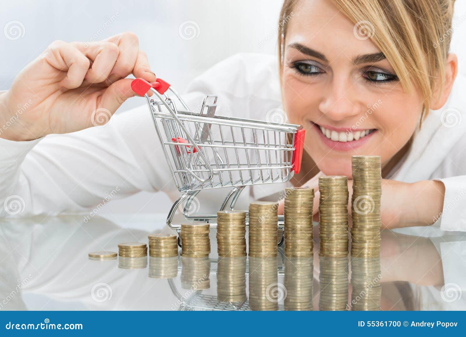 Donna di affari con il mini carrello e monete