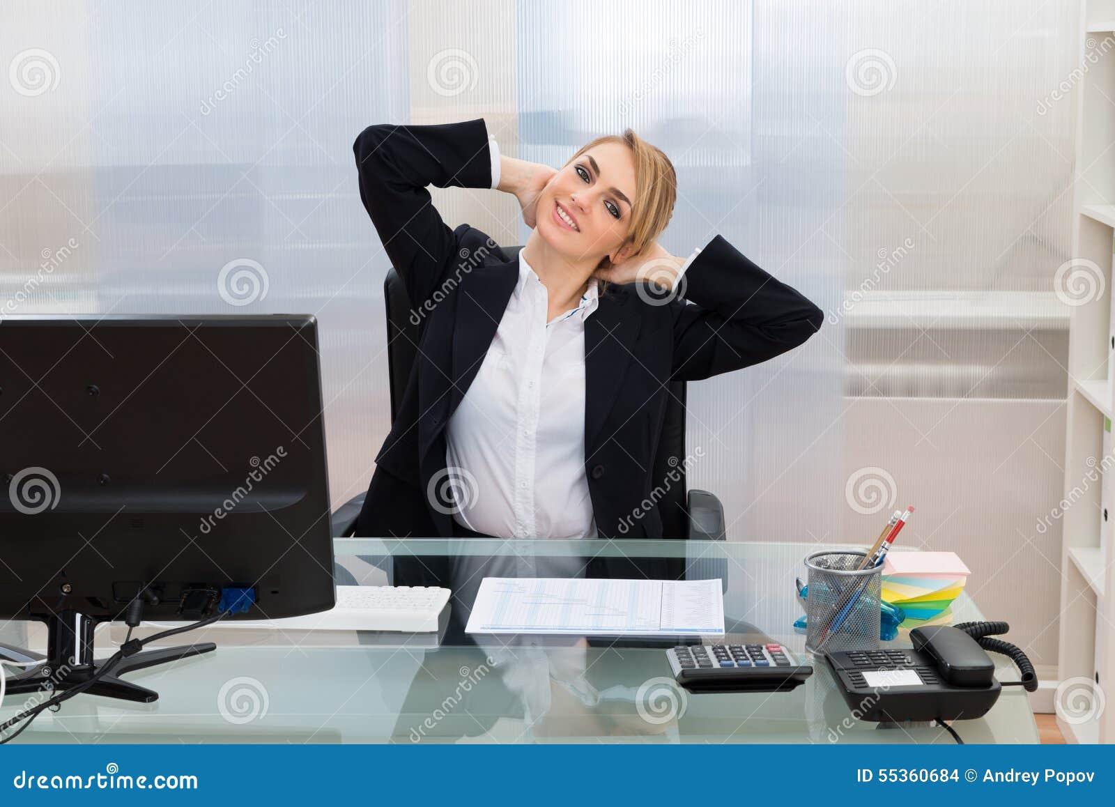 Donna di affari con le mani dietro la testa allo scrittorio
