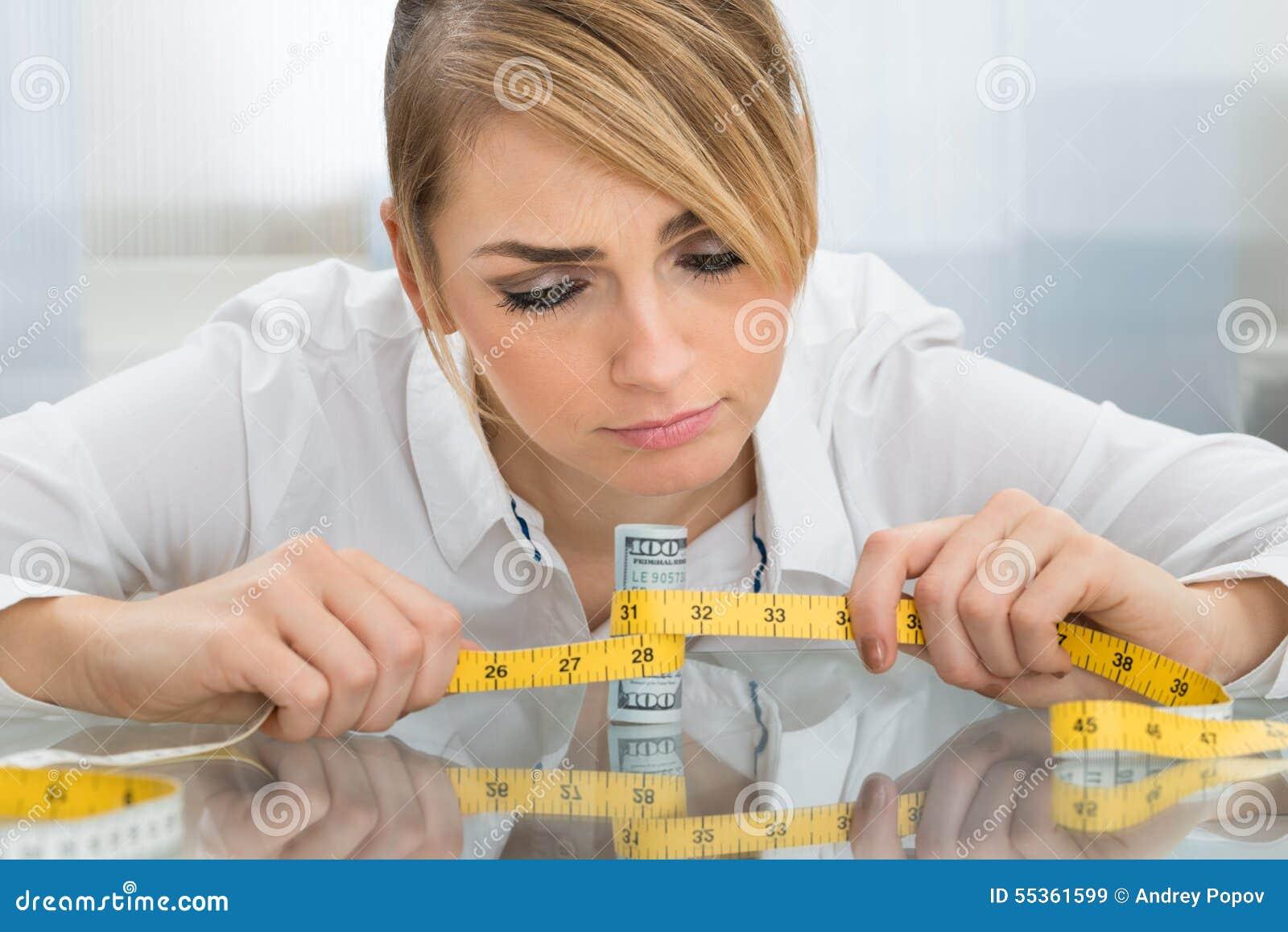 Donna di affari con nastro adesivo e la banconota di misurazione