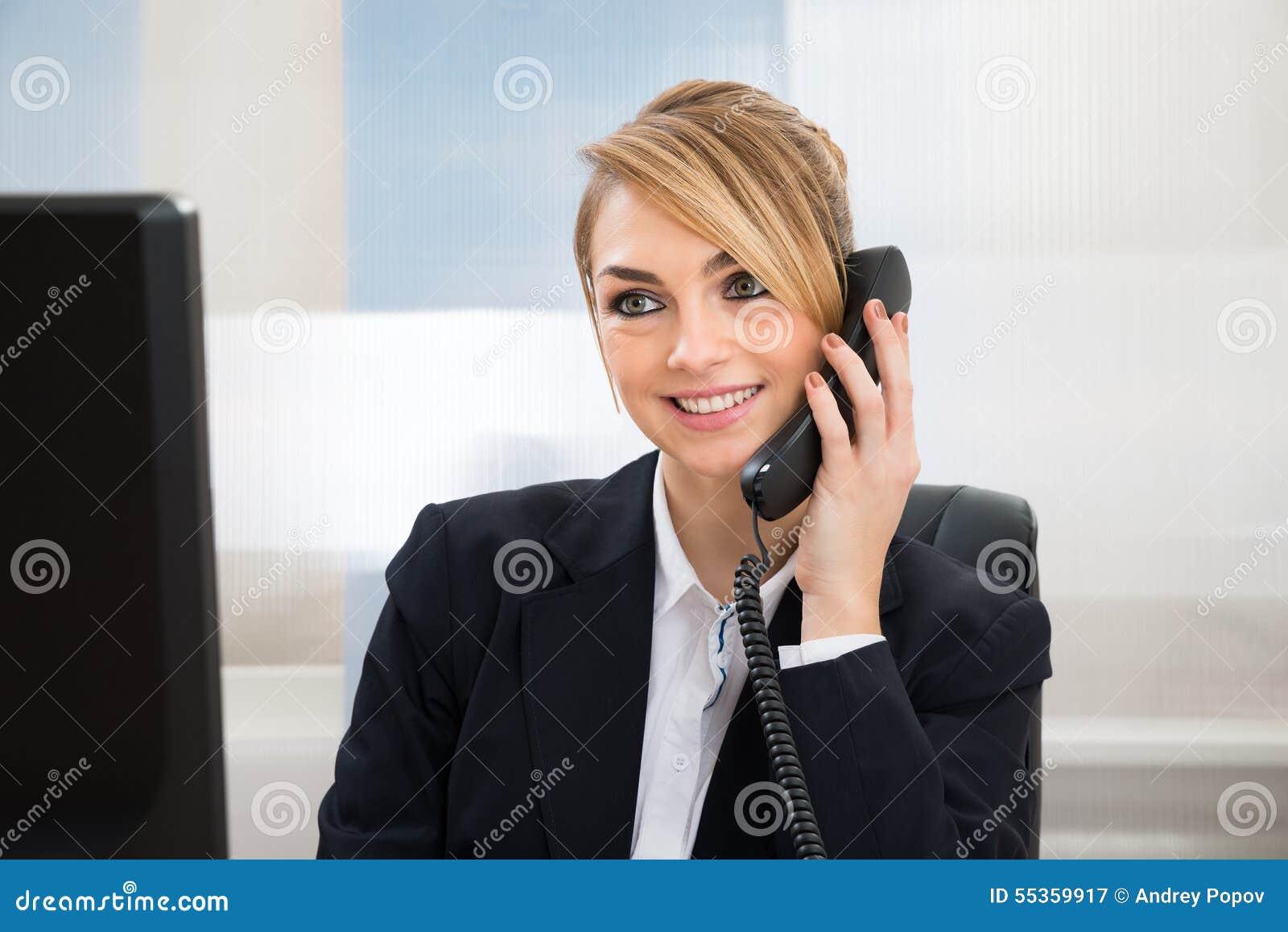 Donna di affari felice che parla sul telefono
