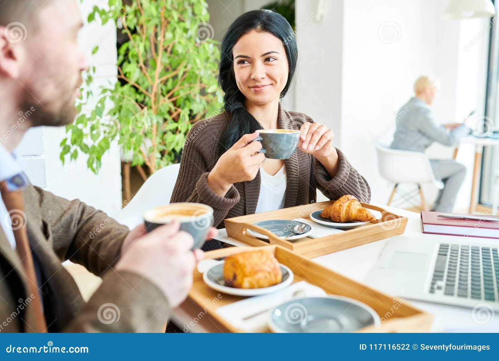 Donna di affari graziosa Enjoying Coffee alla riunione