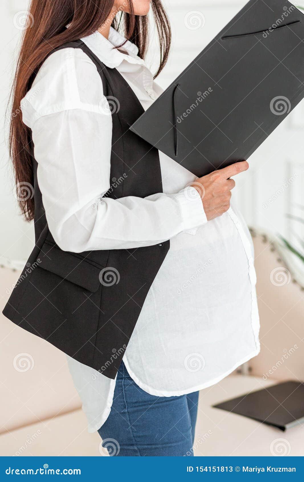 Donna di affari incinta sul lavoro in un ufficio che legge un documento